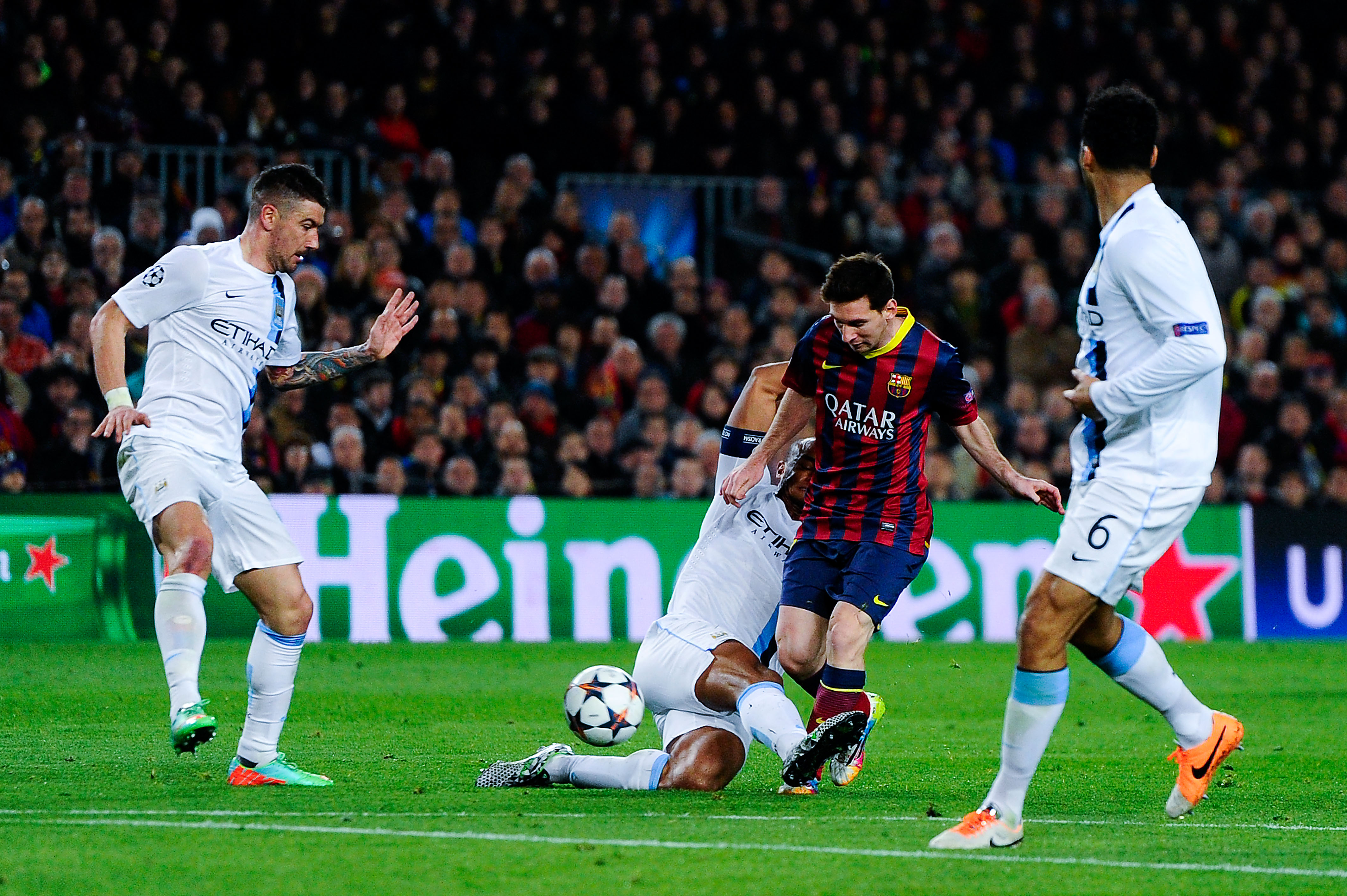 Lionel Messi of FC Barcelona duels for the ball with Vincent Kompany of Manchester City FC during to the UEFA Champions League Round of 16 second leg match between FC Barcelona and Manchester City at Camp Nou on March 12, 2014 in Barcelona, Spain.