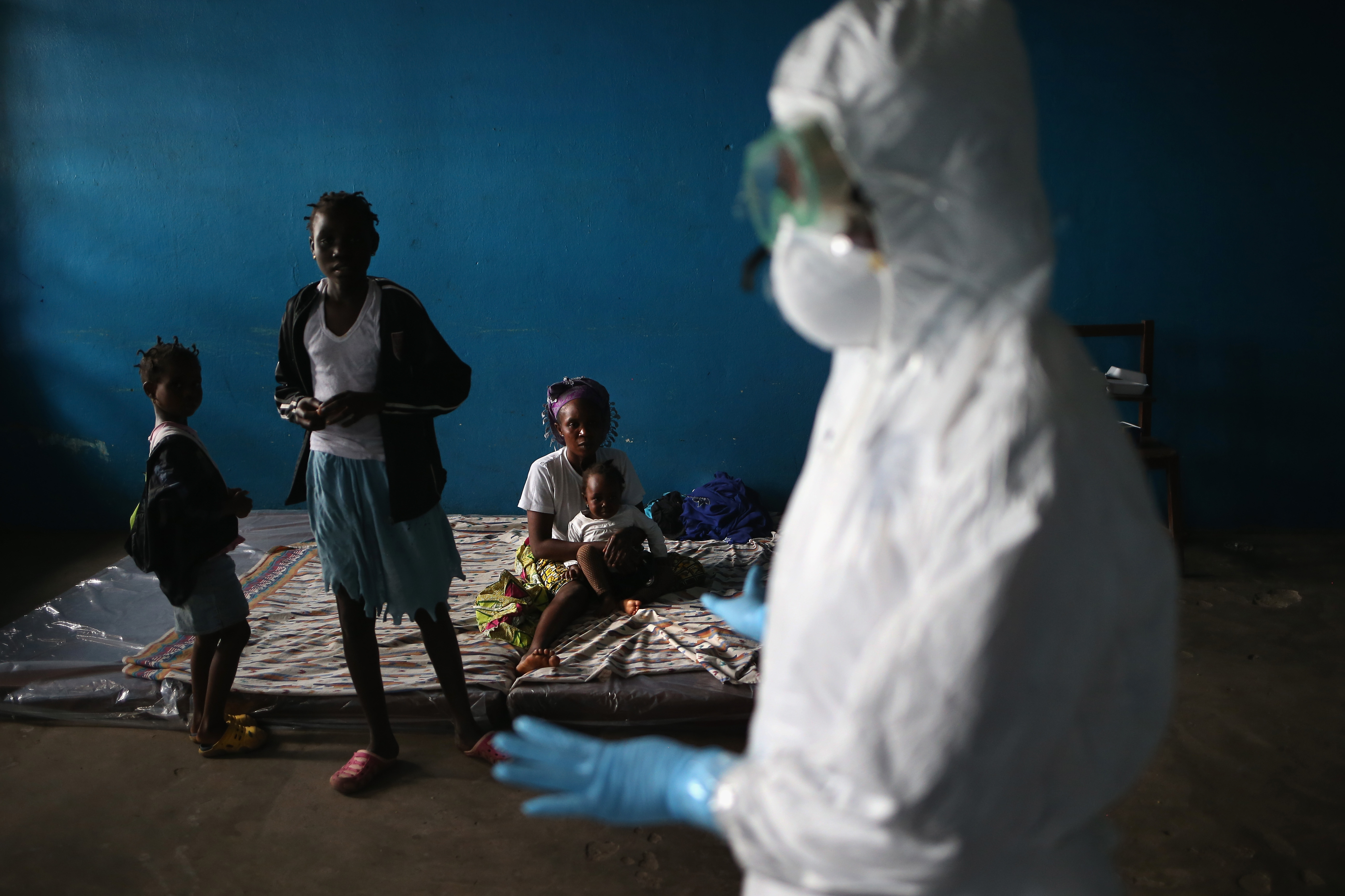 A Liberian health worker speaks with families in a classroom now used as Ebola isolation ward on August 15, 2014 in Monrovia, Liberia.