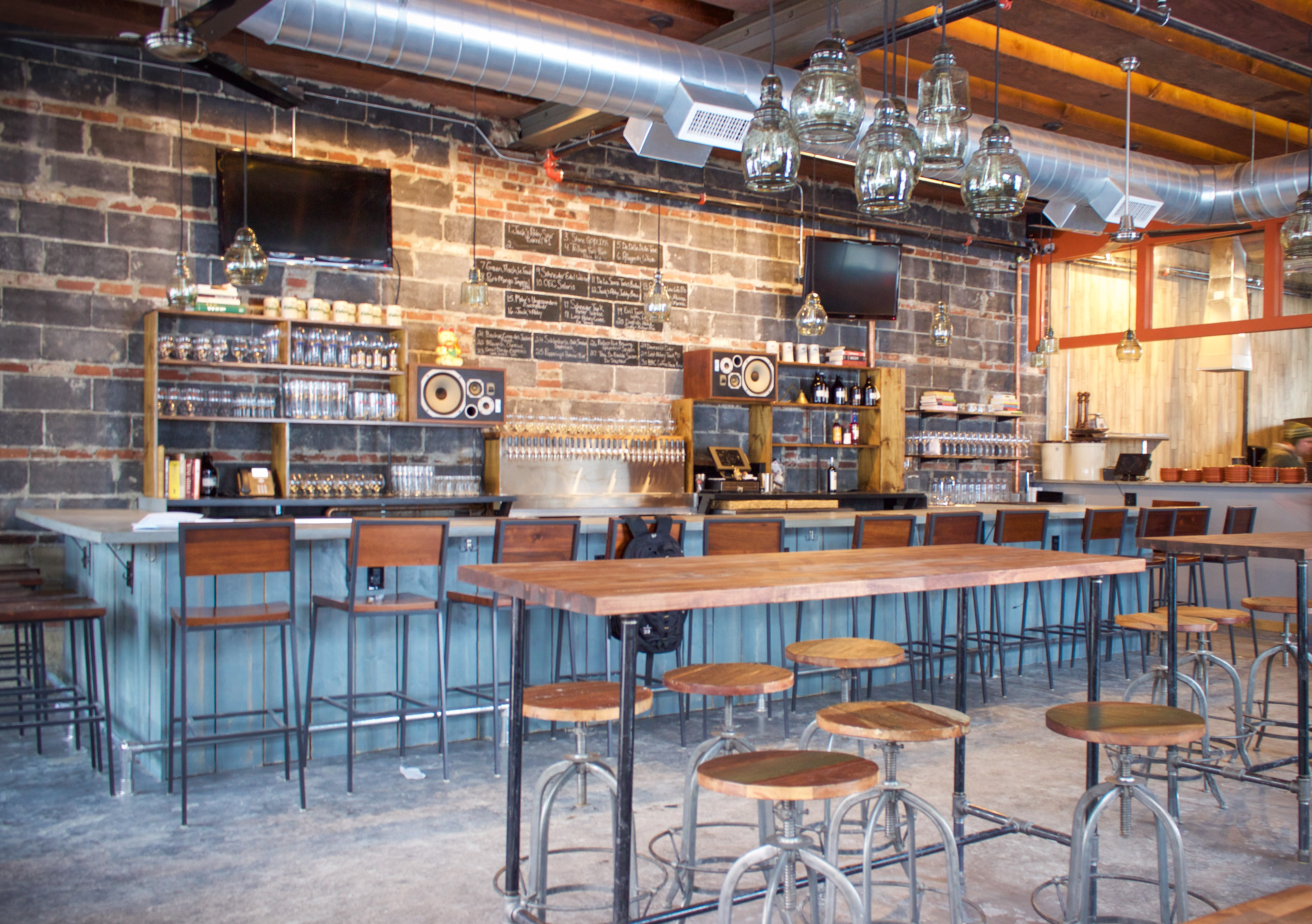 Photo of a restaurant interior, focusing on the bar and high-top tables in front of it. The wall is mostly large gray bricks. Tables and chairs are a medium-colored wood.