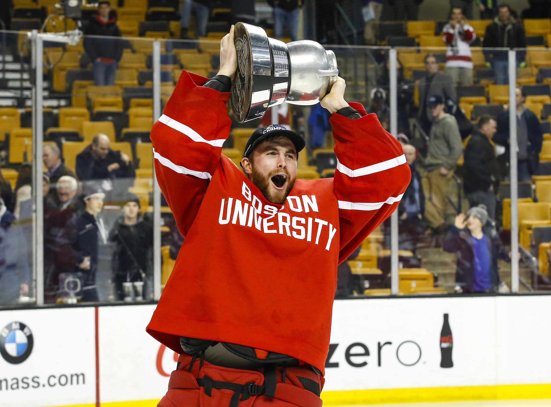 BU goaltender Matt O'Connor lifts the Beanpot above his head in celebration.