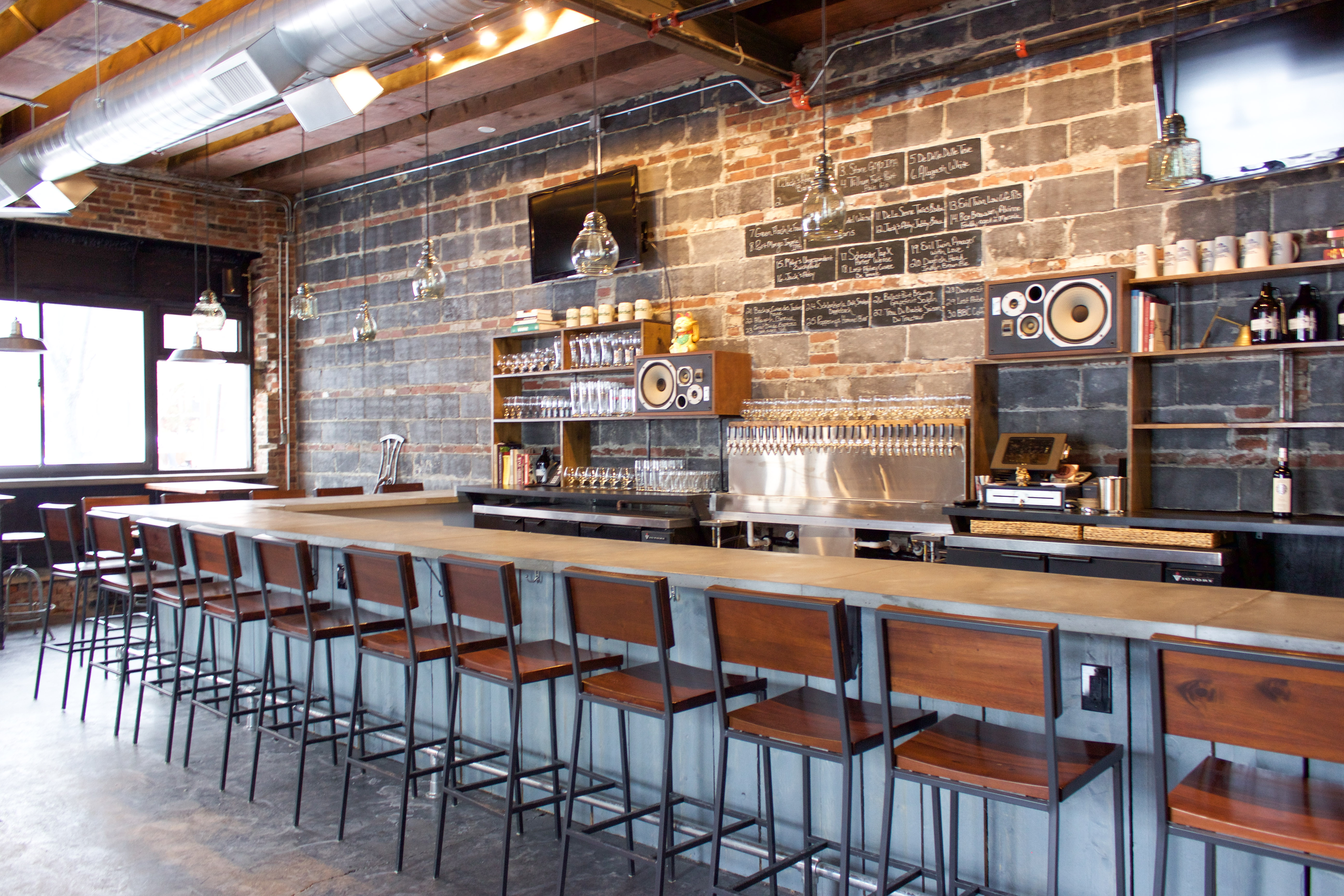 A casual bar at a restaurant with gray bricks along the wall, a polished cement floor, and wooden bar chairs.