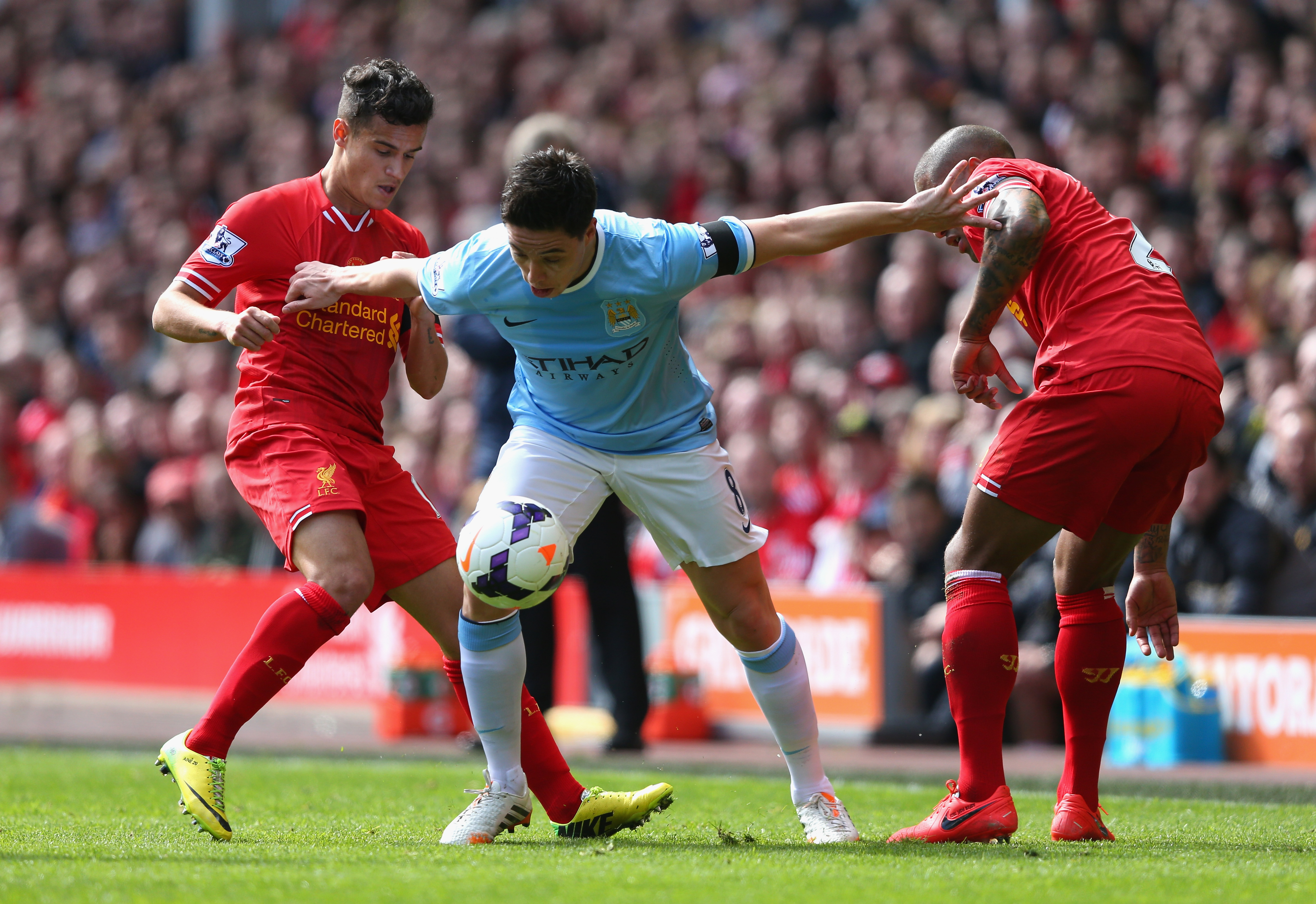 APRIL 13: Philippe Coutinho and Glen Johnson of Liverpool compete with Samir Nasri of Manchester City during the Barclays Premier League match between Liverpool and Manchester City at Anfield on April 13, 2014 in Liverpool, England.