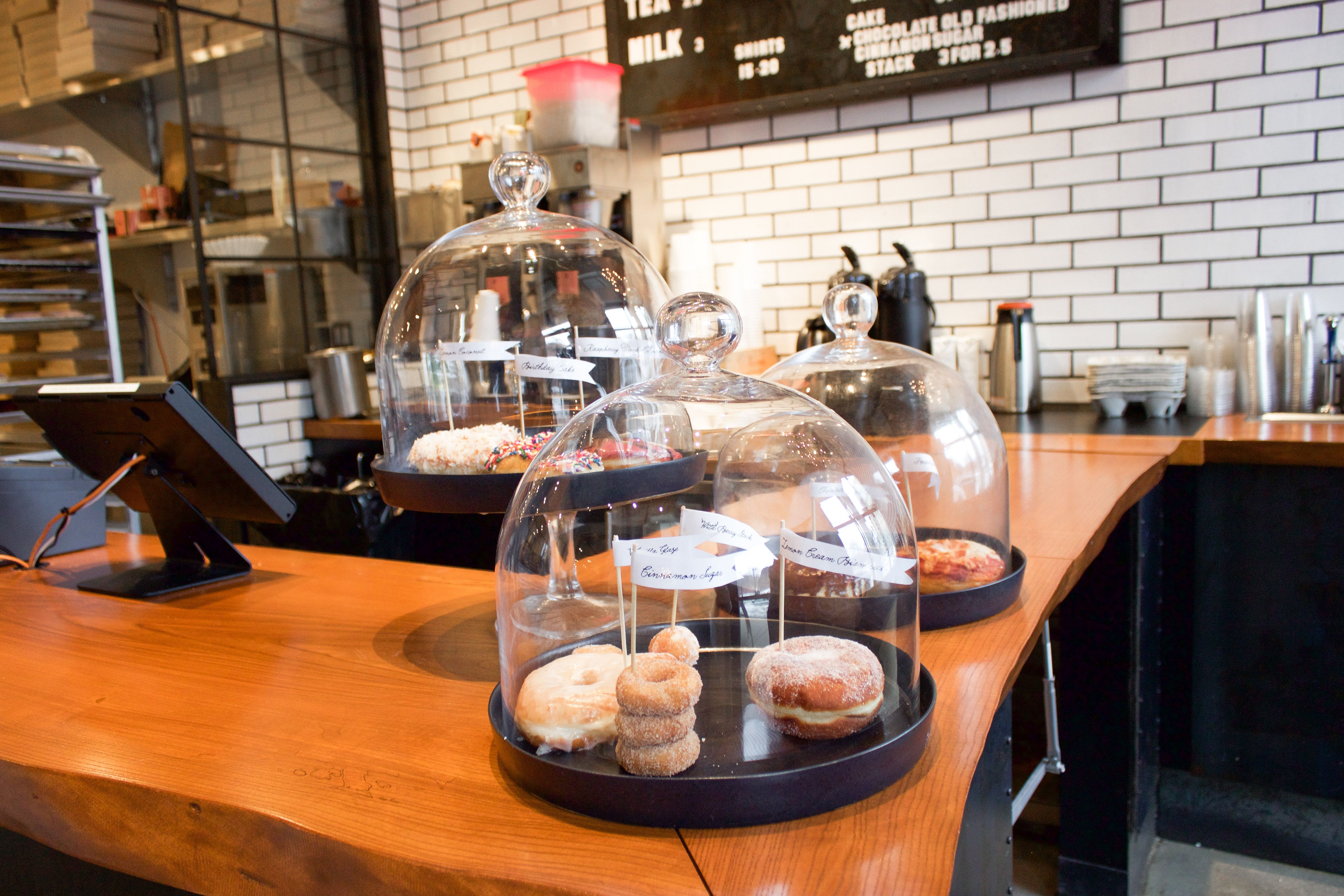 Interior of a doughnut shop. A few doughnuts are visible under a glass dome on the wooden countertop, and white subway tile covers the back wall, where there's a black menu board with white lettering.