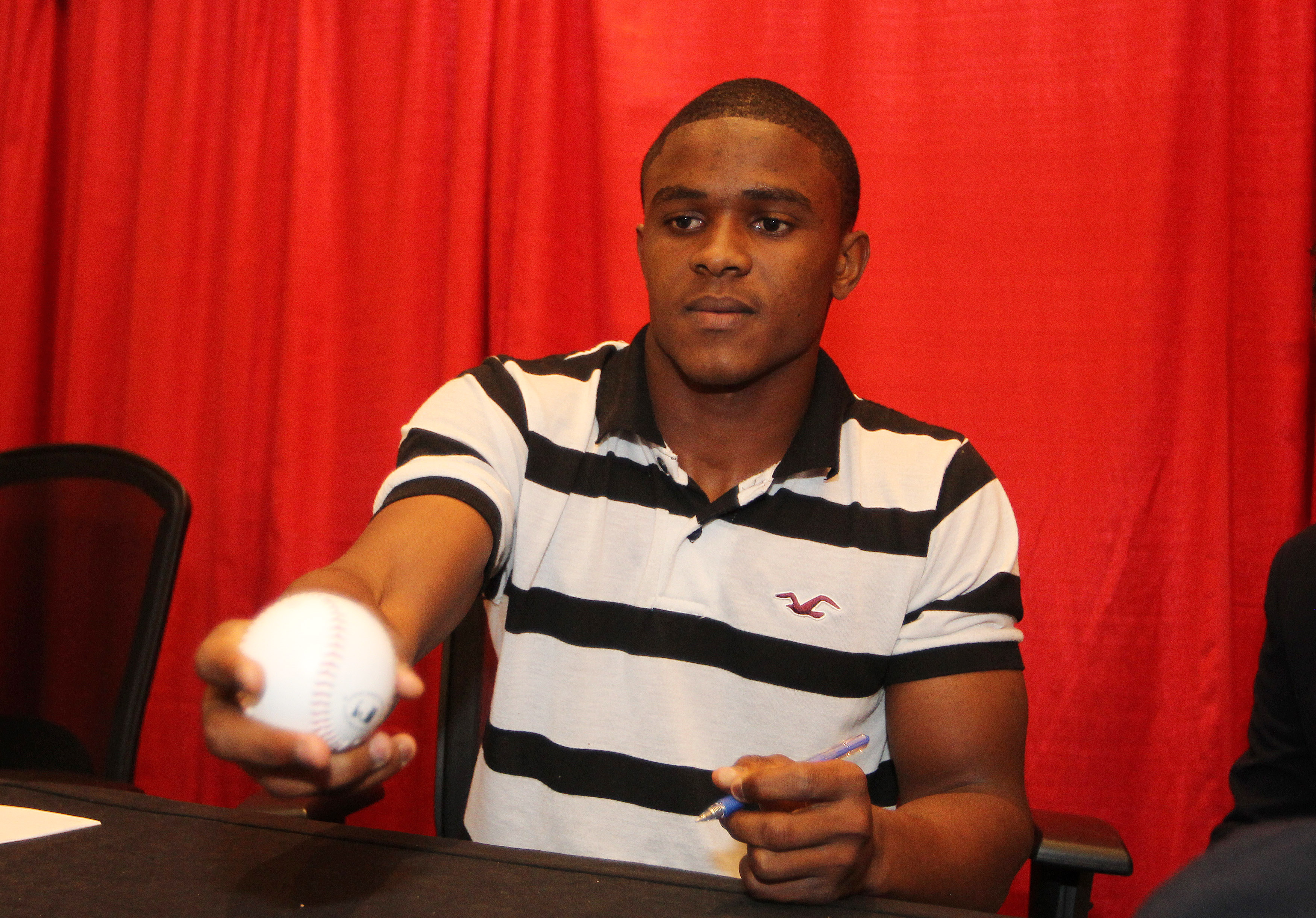 Magneuris Sierra signs a ball at Winter Warm Up.