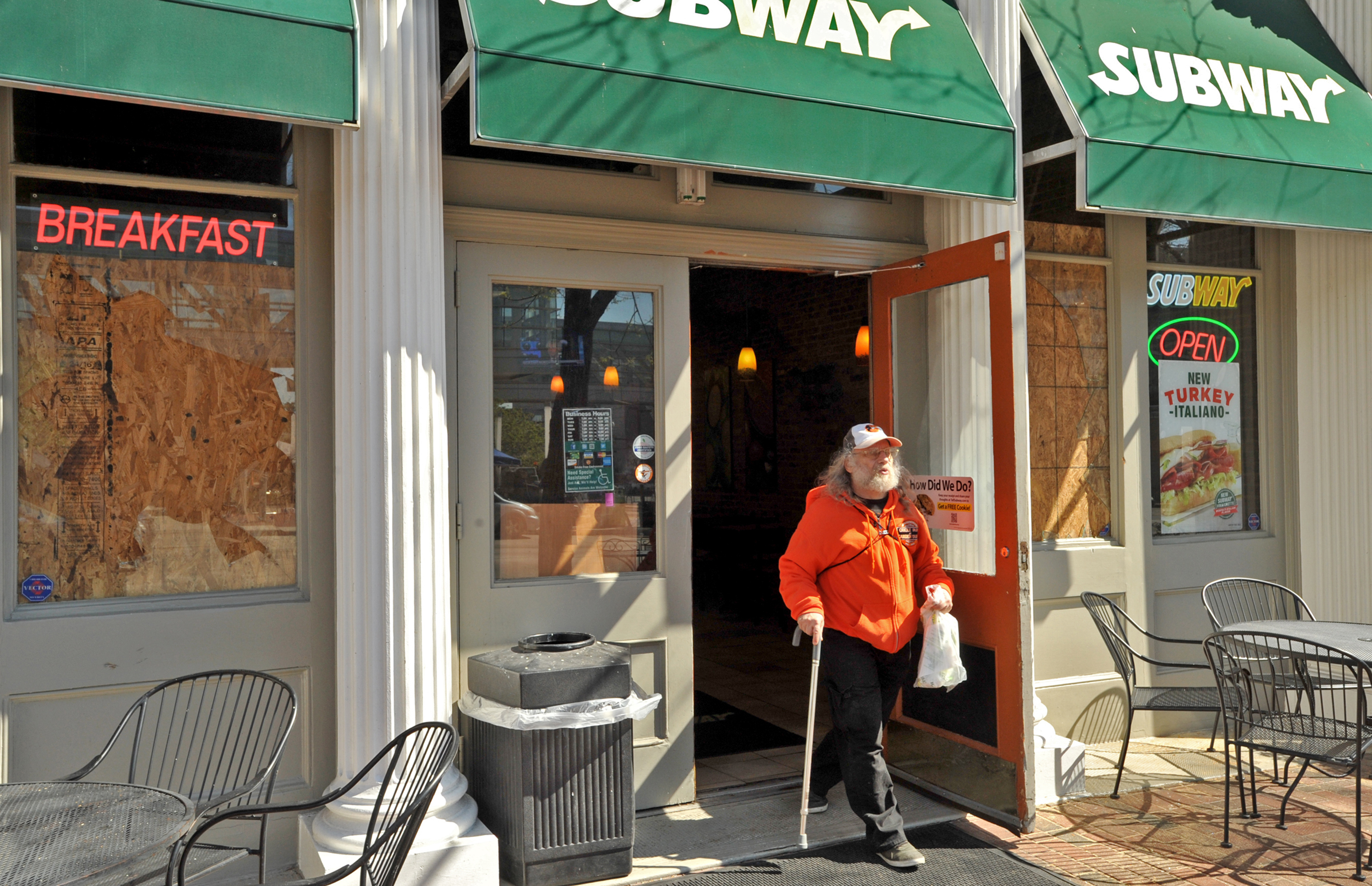 Alan Schwartz stops for food at a Subway restaurant in Baltimore, which was open despite boarded-up windows.