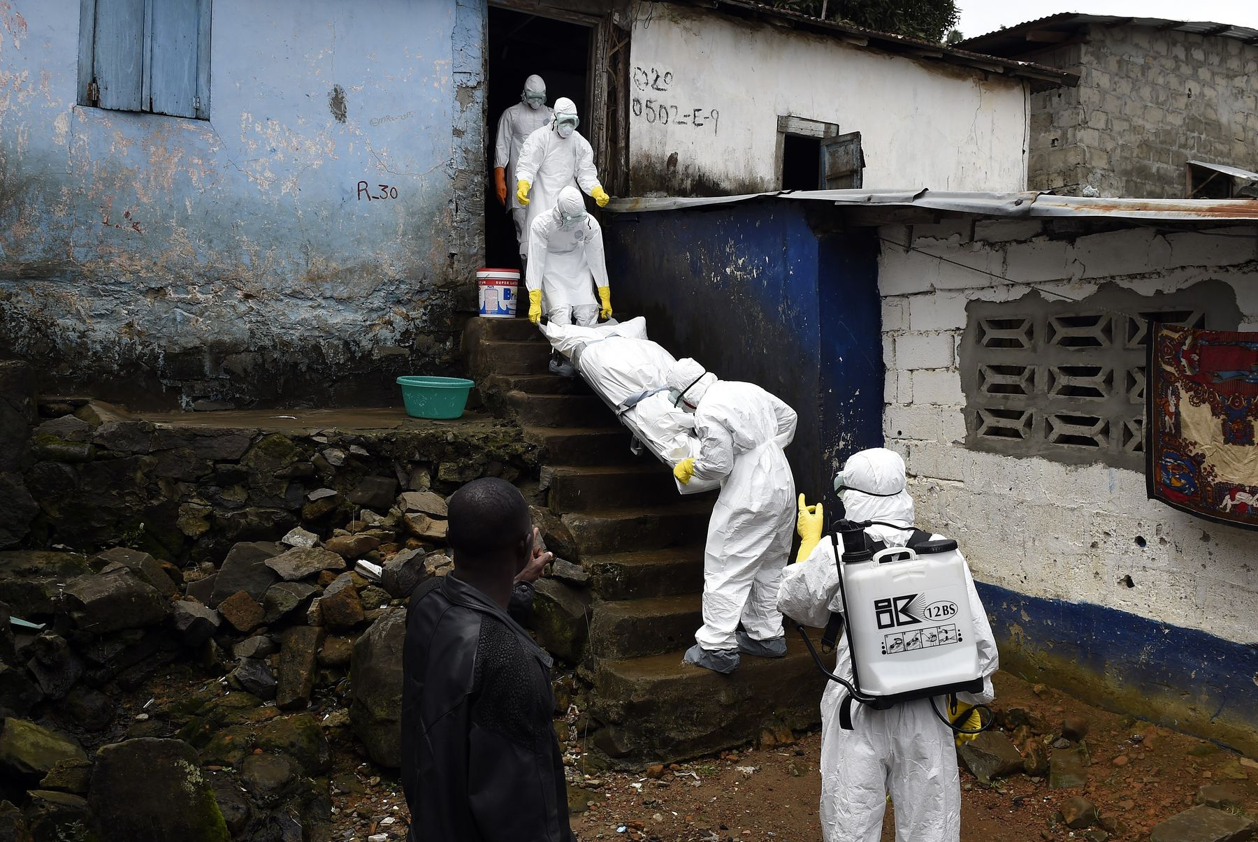 Medical staff remove the corpse of an Ebola victim from a house in Monrovia, Liberia.