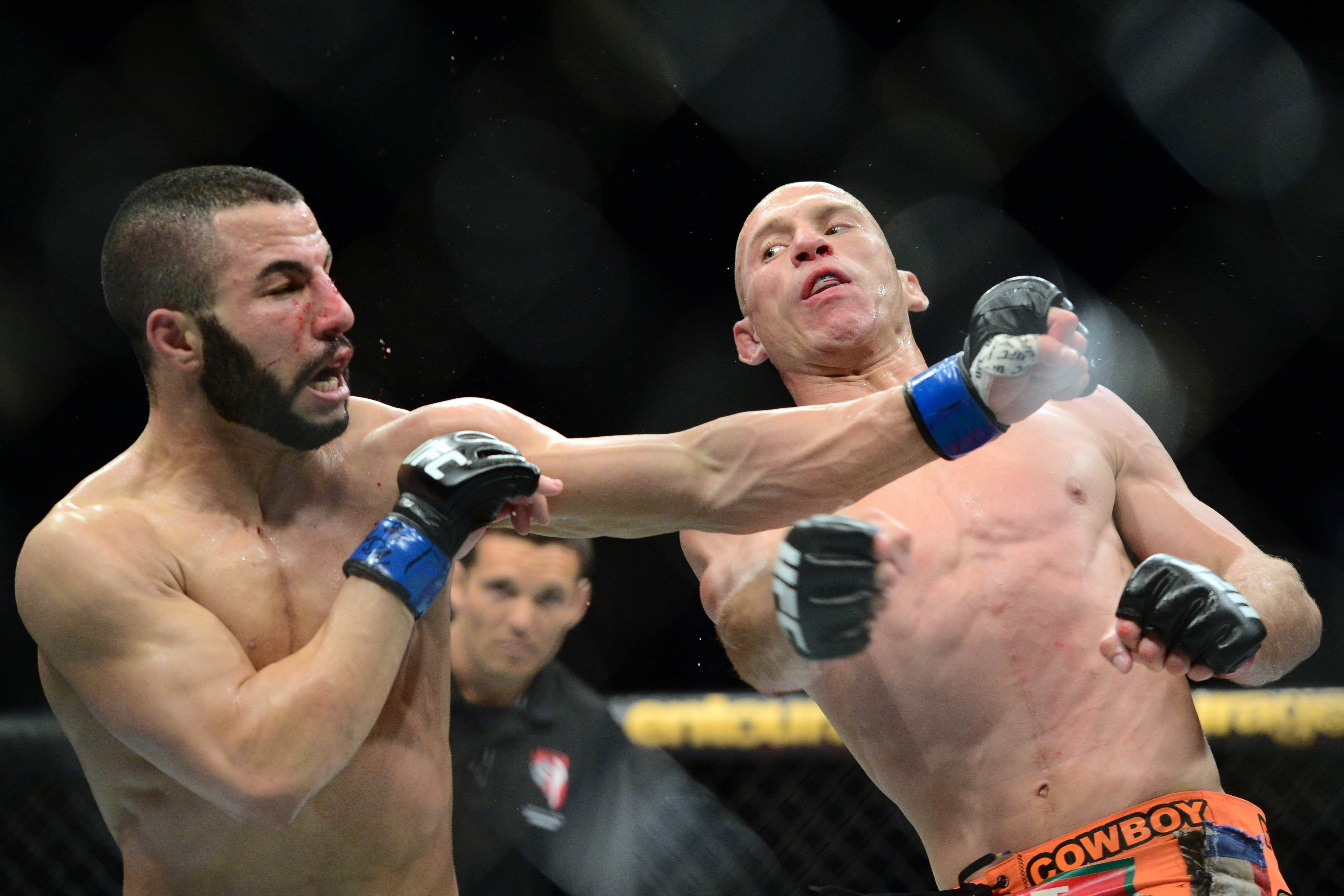 John Makdessi (L) takes a hard shot from Donald Cerrone at UFC 187.