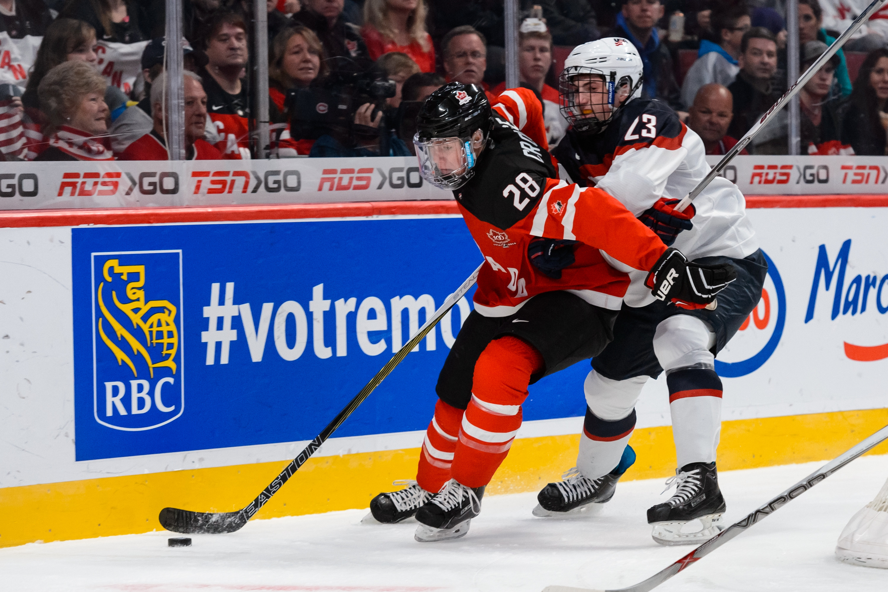 Lawson Crouse #28 of Team Canada shields Zach Werenski #23 of Team USA off the puck at the 2015 WJC.