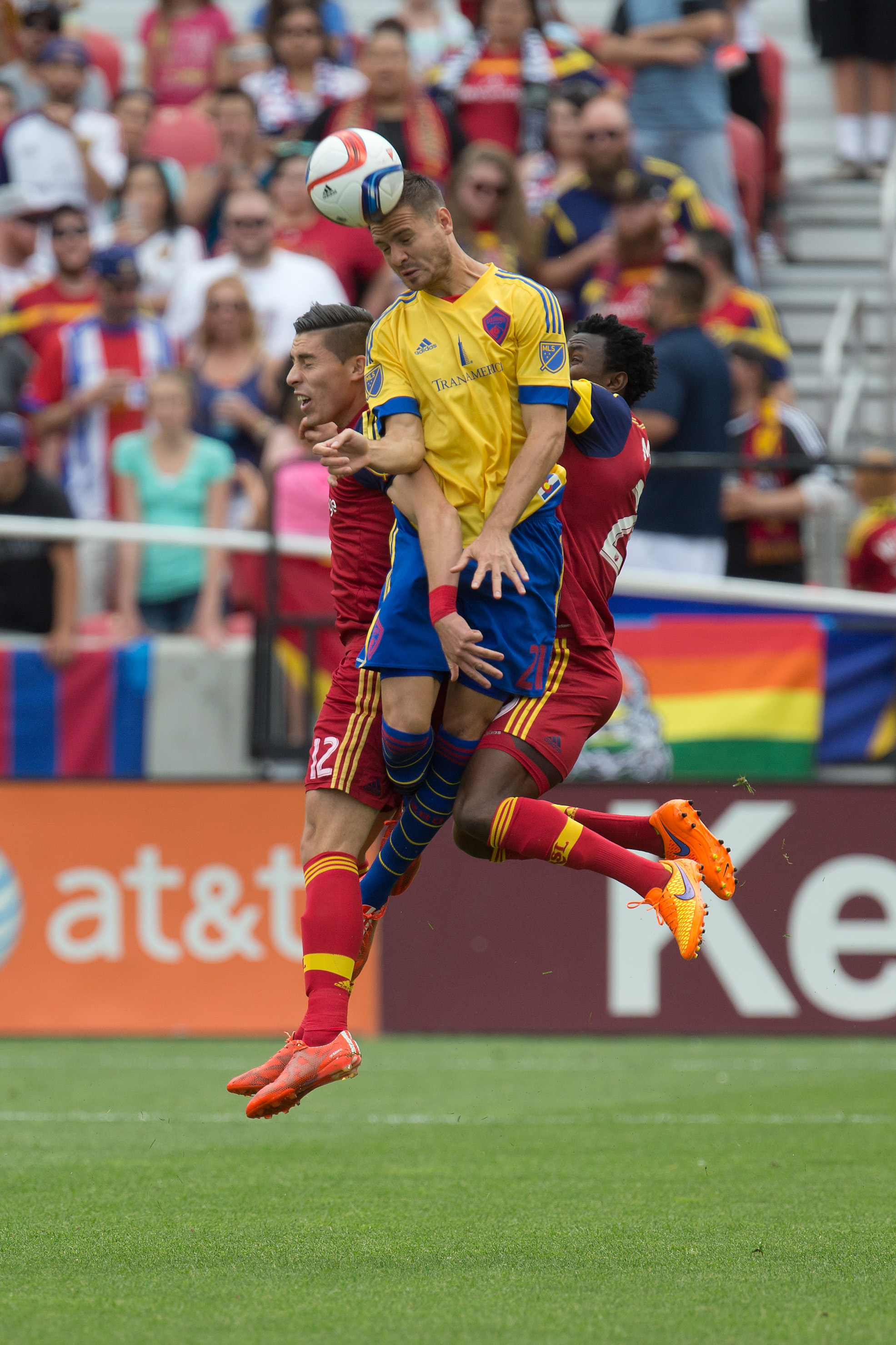 Luis Solignac going up between two RSL defenders and winning control of the ball.