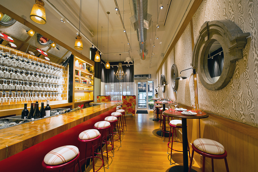 The narrow bar at Corkbuzz, with high-top tables lining the opposite wall