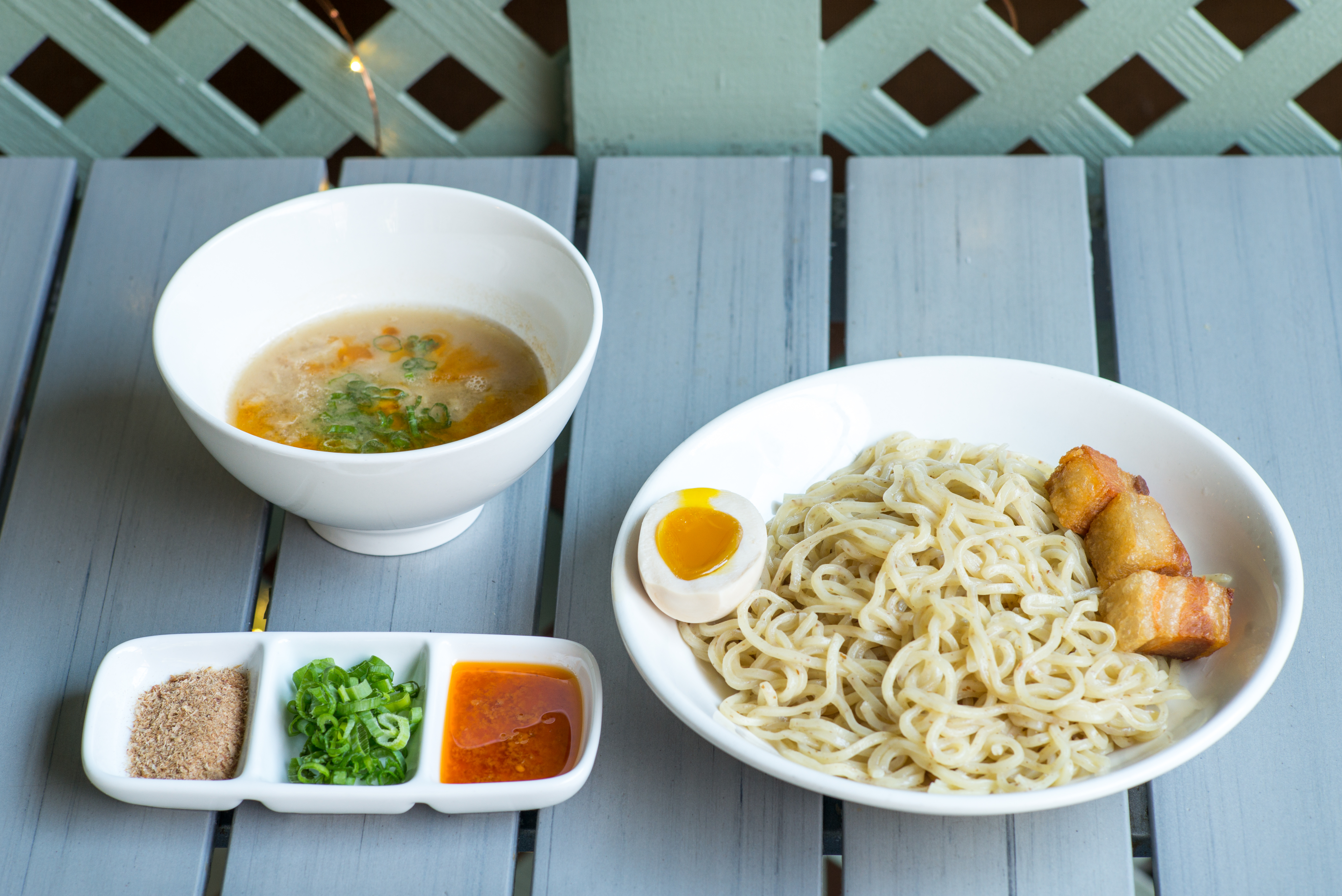 Two bowls, one of tonkotsu broth and another of noodles, sit on an slatted outdoor picnic table. Beside them, a tray of garnishes and colorful sauces.
