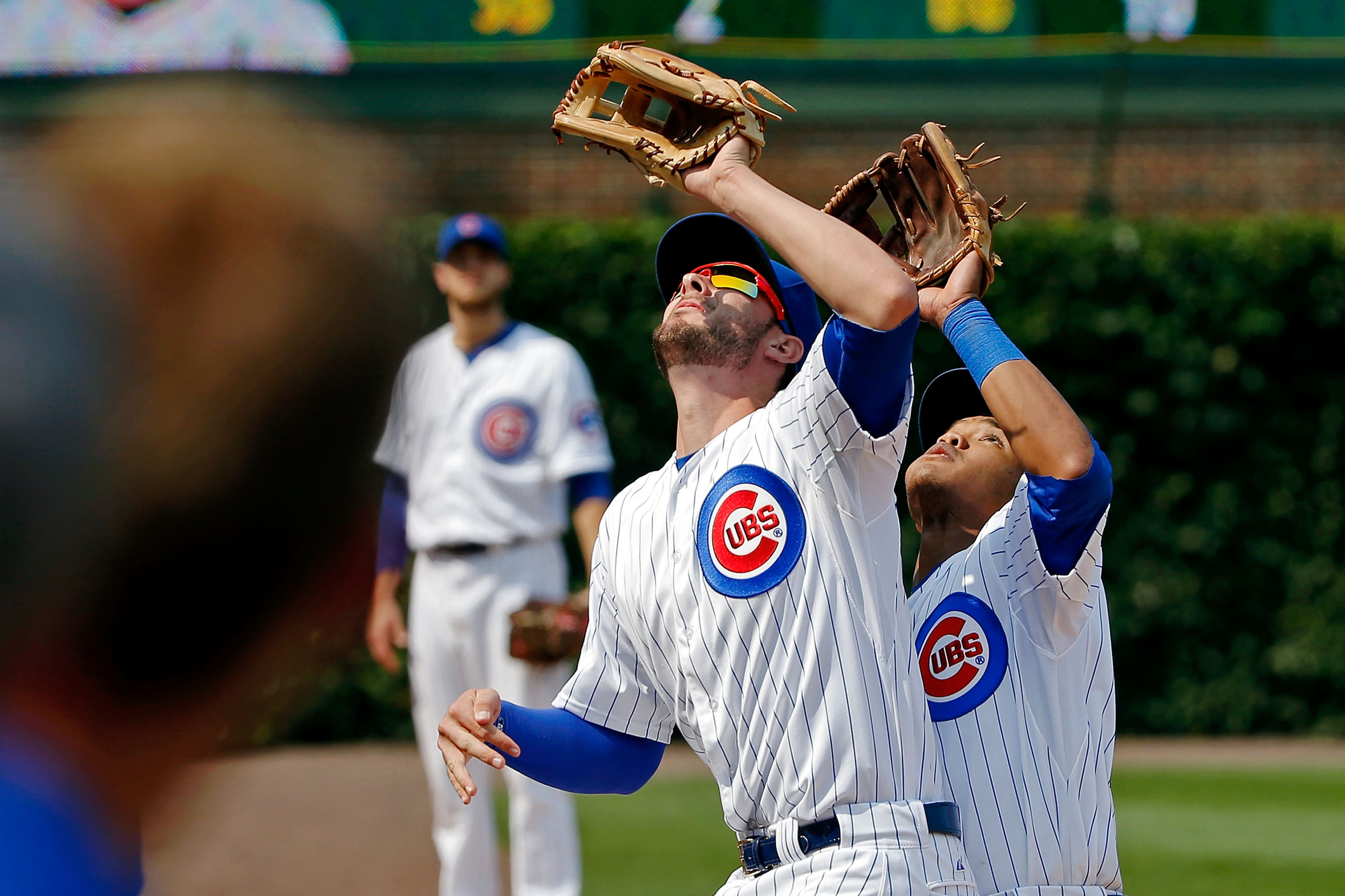 Kris Bryant and Addison Russell go for the ball
