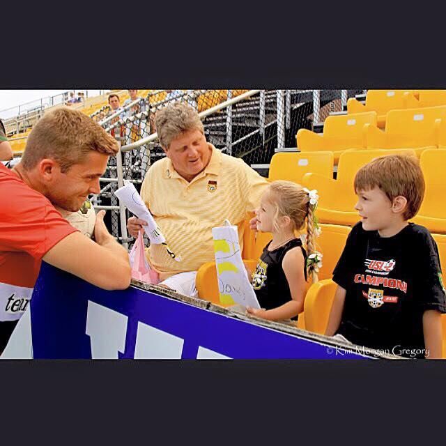 Austin Savage chats with a young fan before a match this season at MUSC Health Stadium.