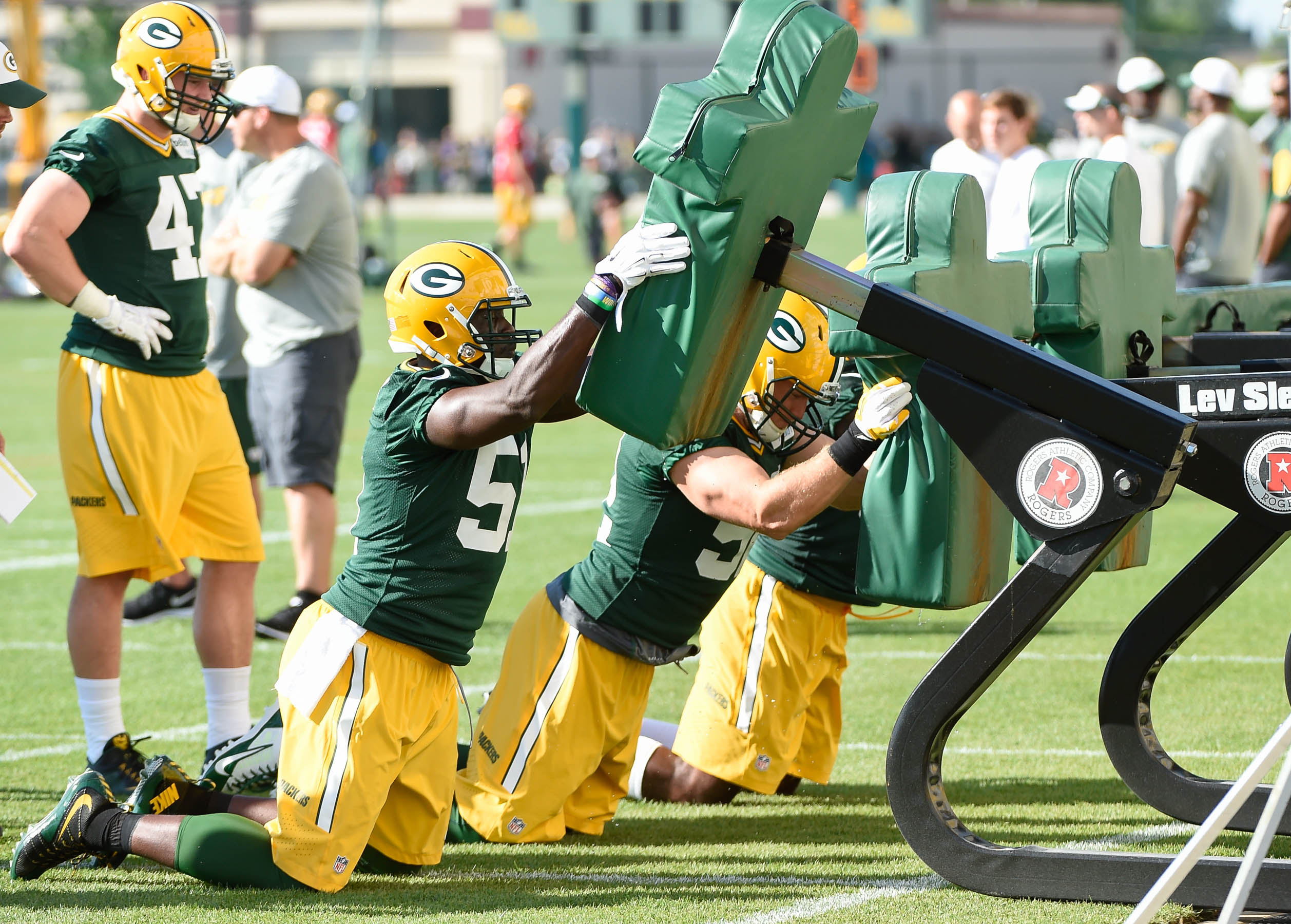 Nate Palmer (center) practices with a blocking sled while Jake Ryan (left) looks on.