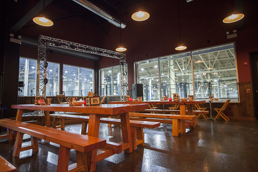 A large taproom space with long wooden tables and benches. Brewing equipment is visible through large windows.