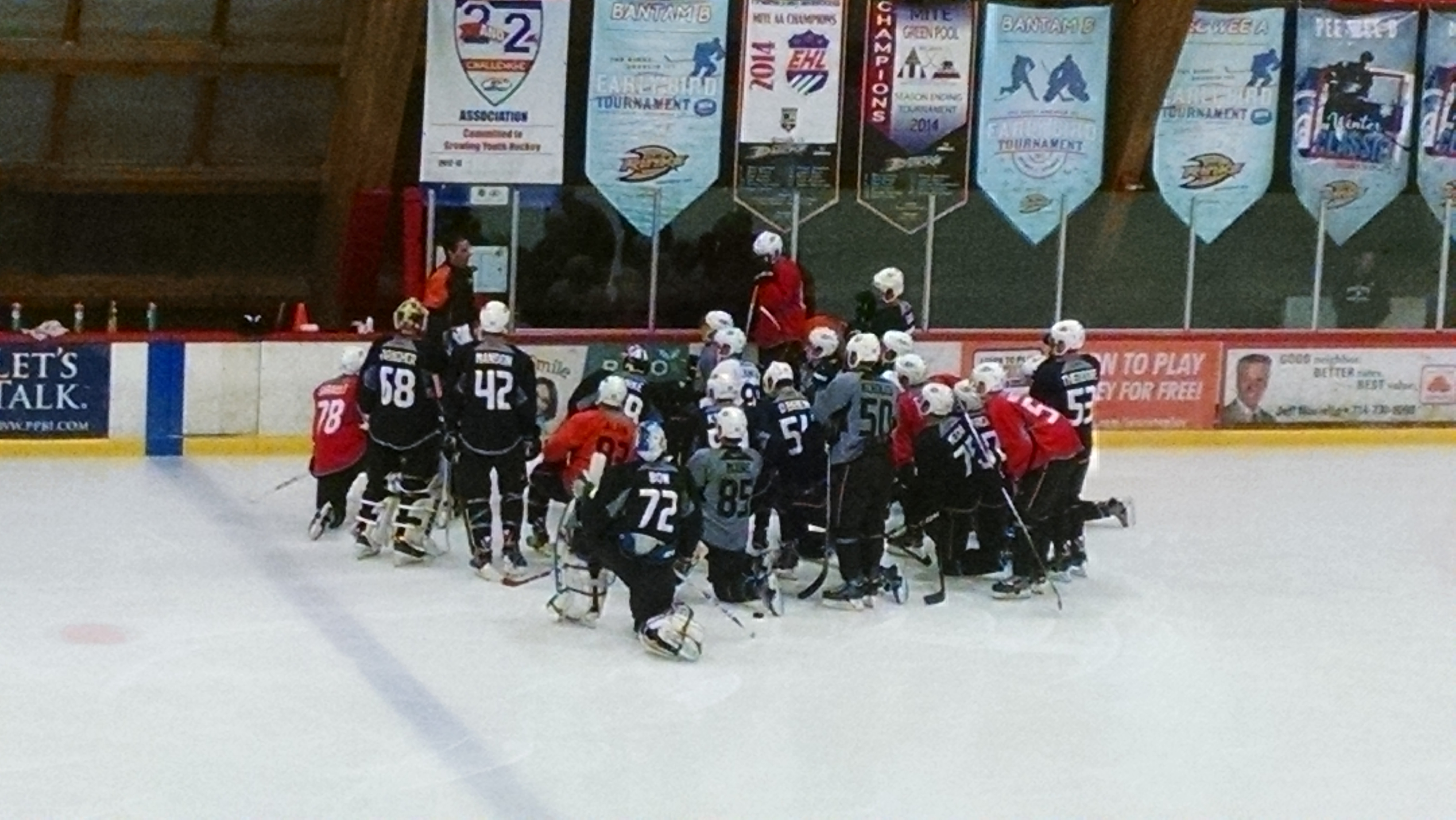 Players gather for instruction before a drill at The Rinks: Anaheim Ice.