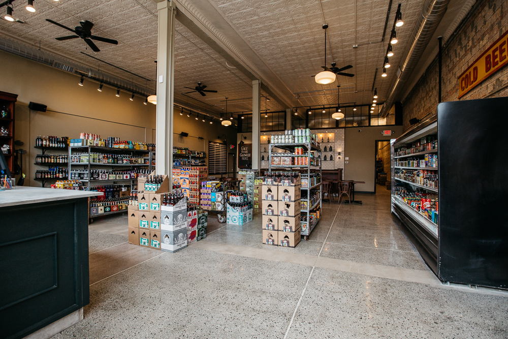 The interior of 8 Degrees Plato features shelves and refrigerated cases full of beer with tin ceilings and black fans.