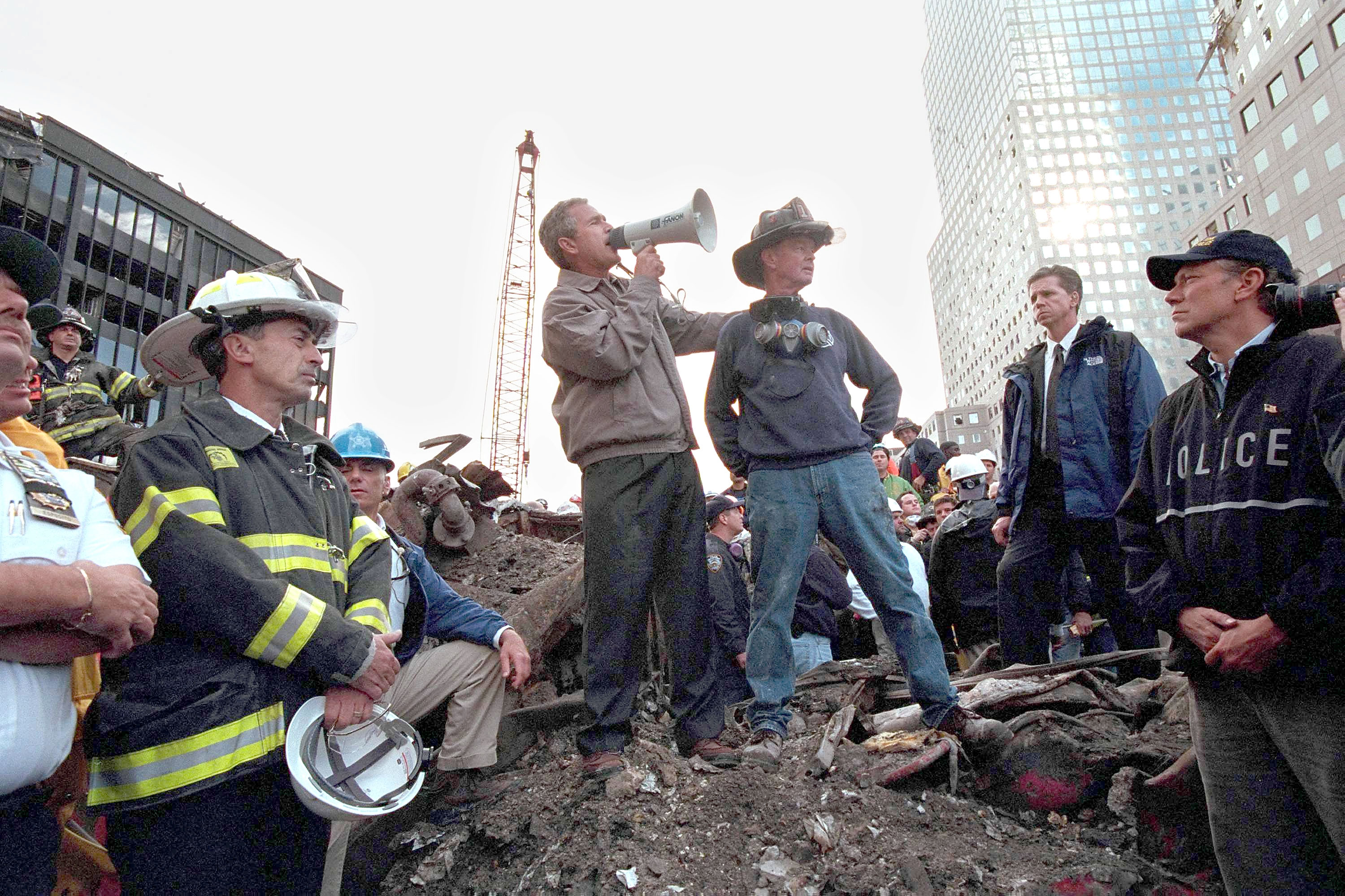 U.S. President George W. Bush speaks to rescue workers, firefighters and police officers from the rubble of Ground Zero September 14, 2001 in New York City. Standing with Bush is retired firefighter Bob Beckwith and at (R) is New York Governor Georg