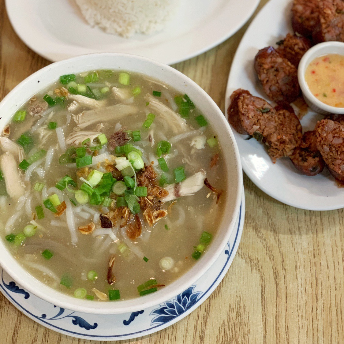 On the left — a large bowl of Lao chicken noodle soup, on the right — sliced spicy sausage and sauce on a platter