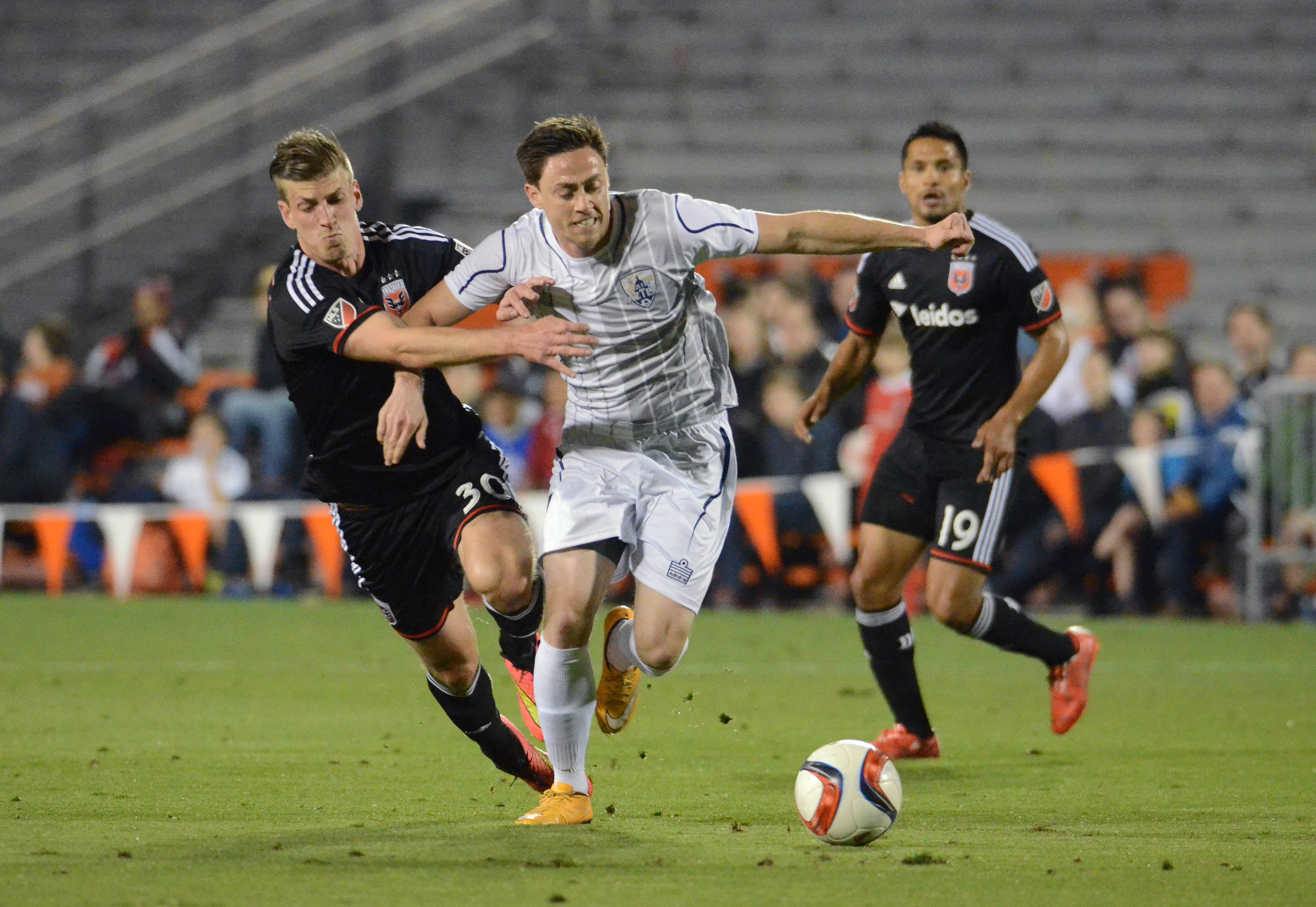 Feb 13, 2015; Austin, TX, USA; DC United forward Conor Doyle (30) fights for possession against Austin Aztex midfielder Brendan King (right) during the first half at Mike A. Myers Stadium. Mandatory Credit: Brendan Maloney-USA TODAY Sports