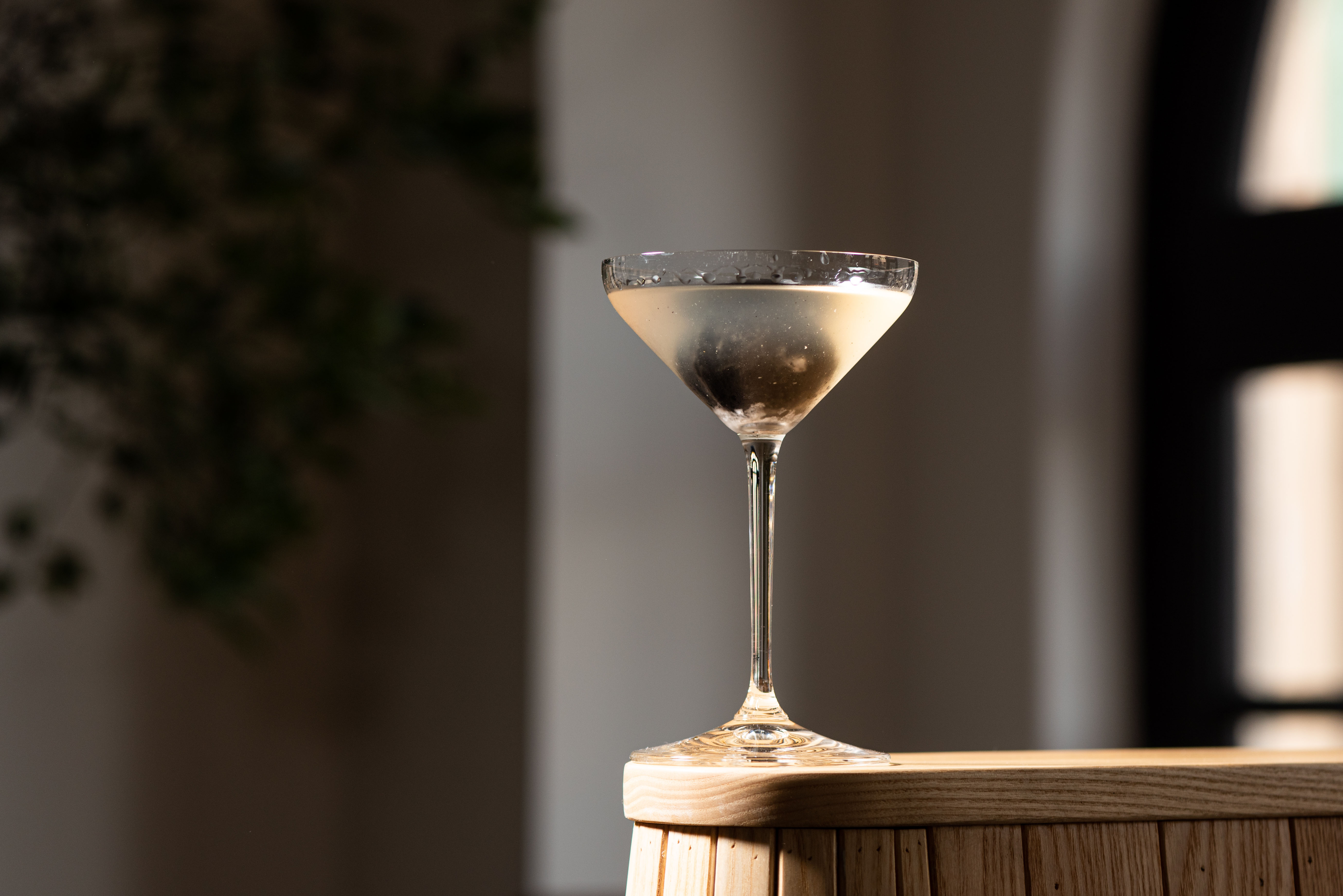 A martini with dark ice at the edge of a table.