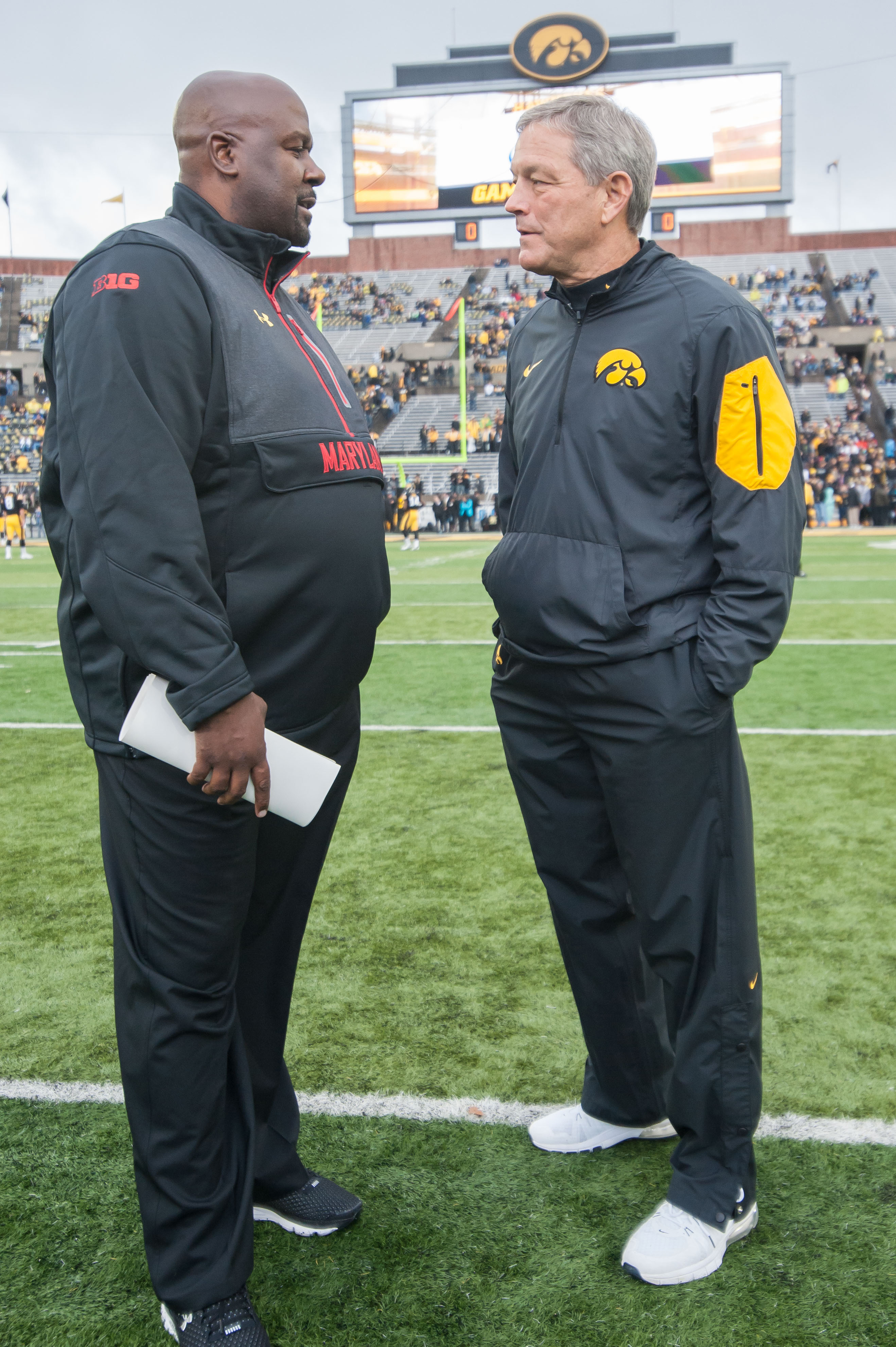 Kirk Ferentz chatting with a young'un, interim Maryland head coach Mike Locksley