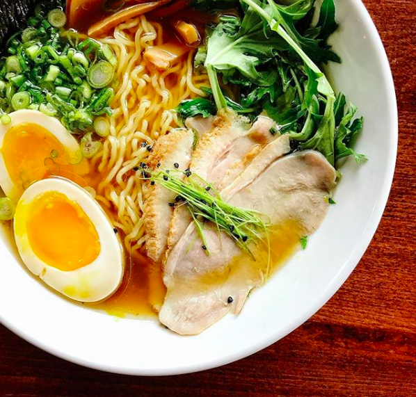 A bowl of ramen with an egg, noodles, scallions, bok choi and slices of duck