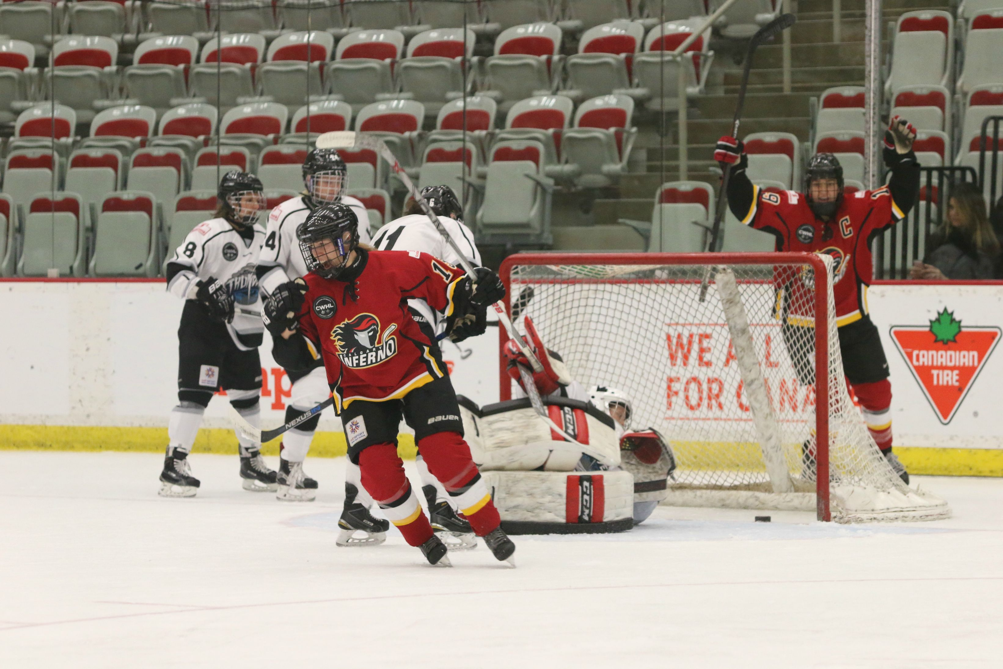Elana Lovell (center in red) celebrates her first goal of the night, which put the Inferno up 2-0 on Brampton. Lovell scored twice Saturday night, putting her further ahead in the CWHL's scoring race.