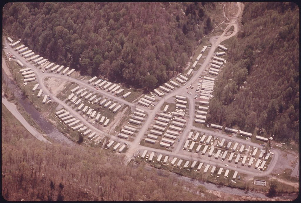 """Aerial view of mobile homes set up after the Buffalo Creek flood. Photo via <a href=""""https://commons.wikimedia.org/wiki/File:AERIAL_VIEW_OF_CLUSTERED_MOBILE_HOMES_USED_BY_FAMILIES_WHOSE_HOUSING_WAS_WIPED_OUT_IN_THE_EARLY_1970'S_WHEN_AN..._-_NARA_-_5"""