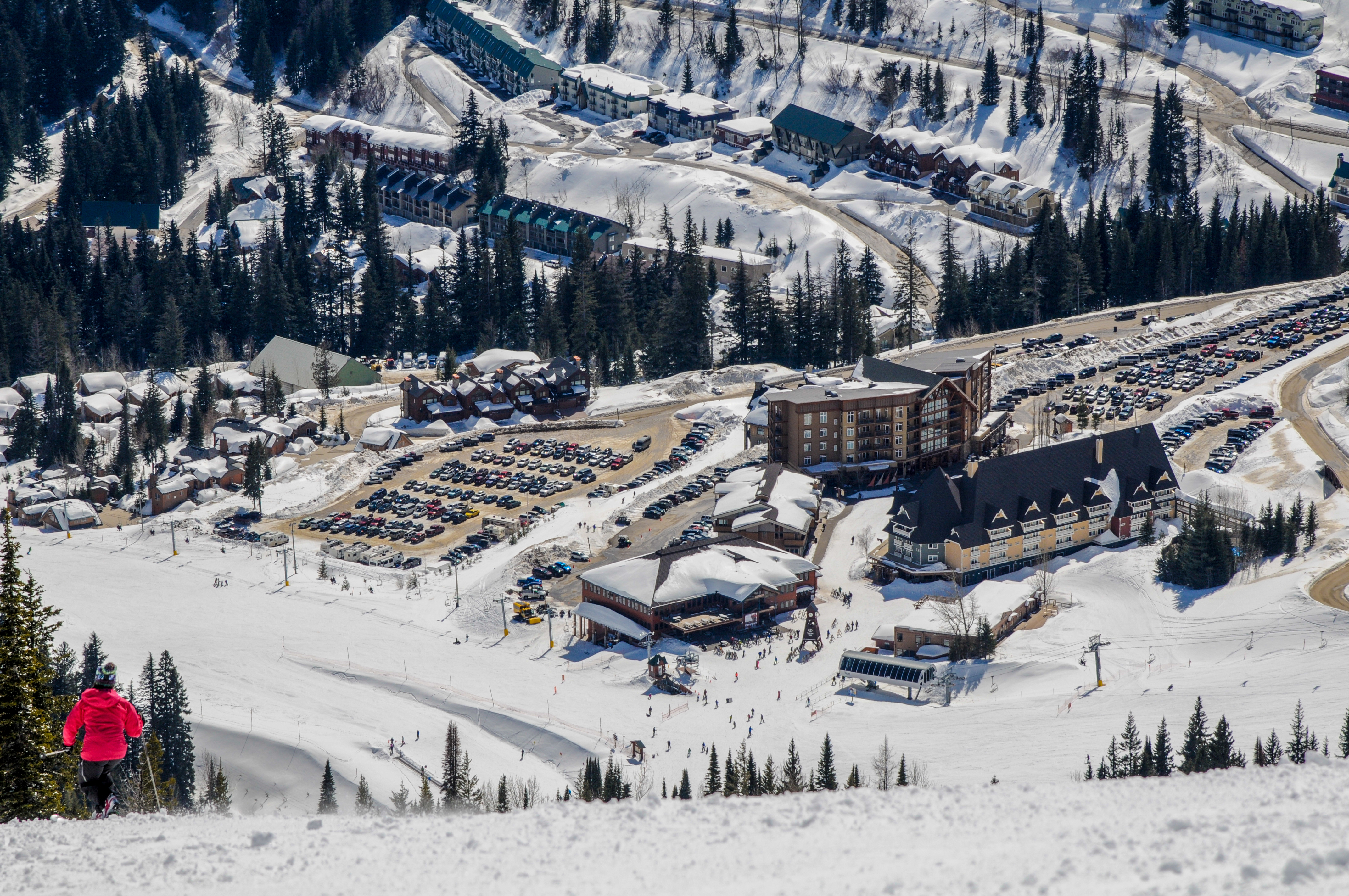 An aerial view of a ski area parking lot from a ski run. There is snow surrounding cars in parking lots, and multiple lodges at the base area.
