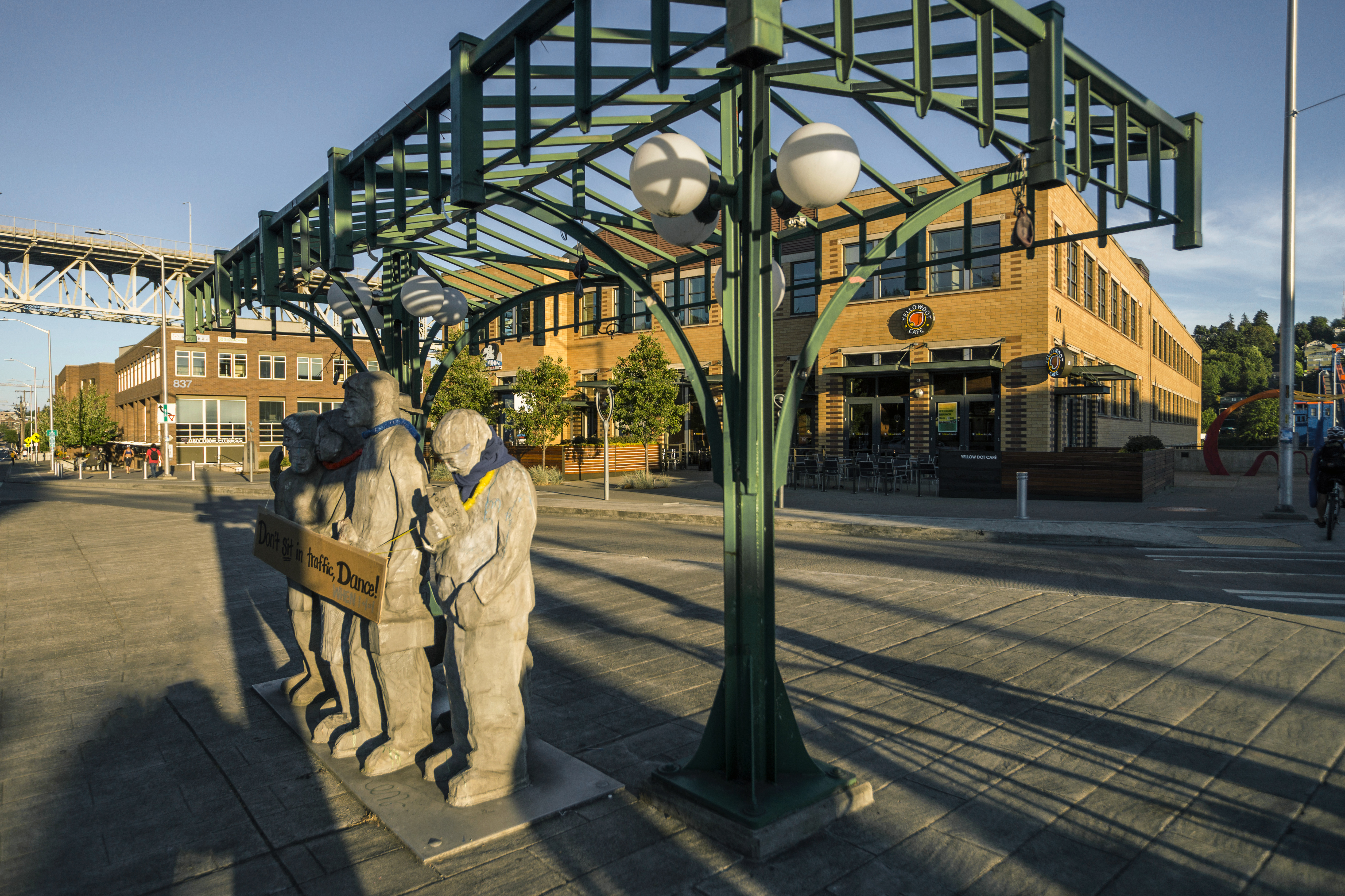 Stone figures stand beneath an iron-and-glass shelter that looks like a bus stop. There's a street and a brick building in the background.