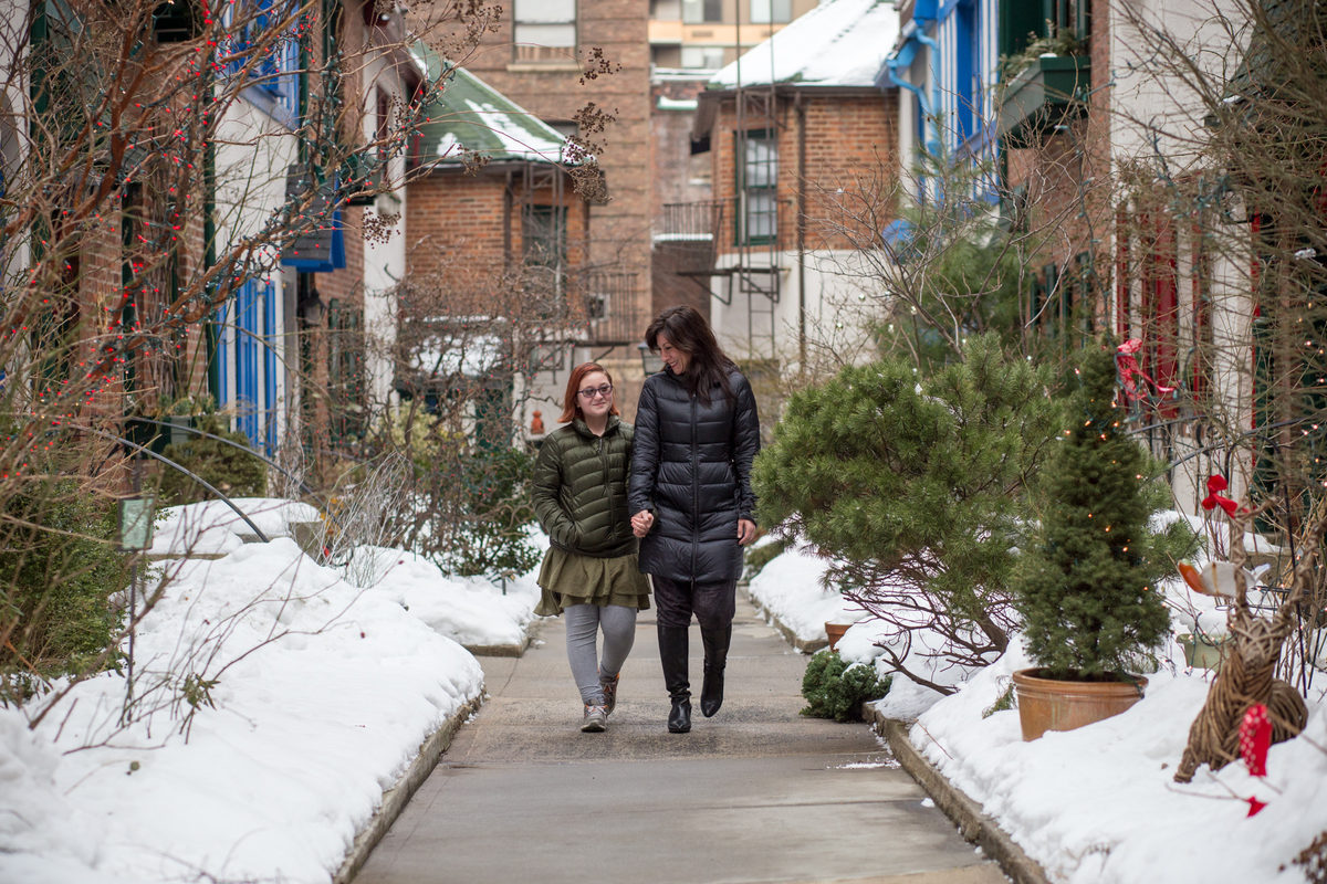 Two people walk down a path. On both sides of the path are red brick attached houses.