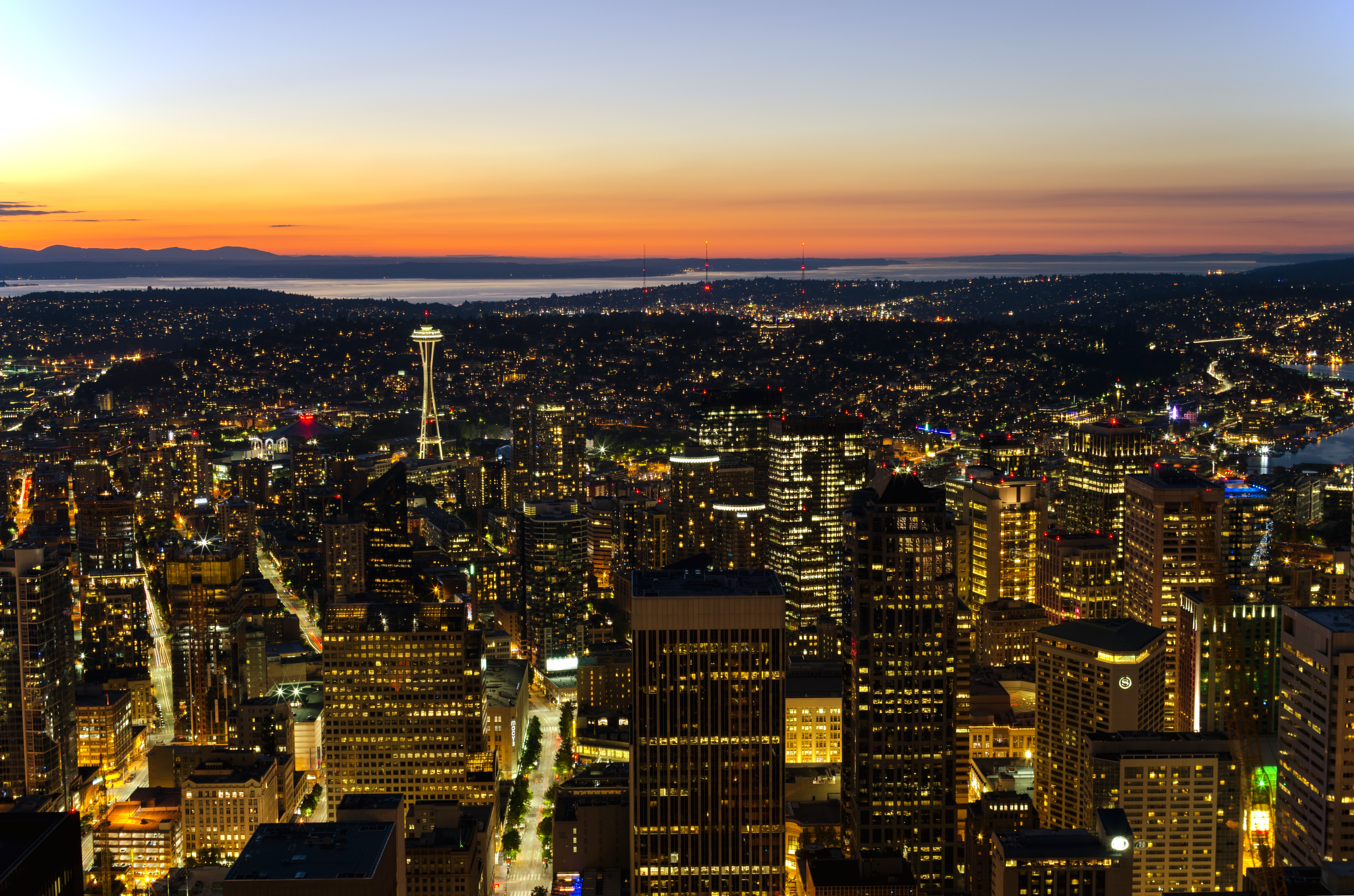 An aerial view above the city of Seattle at sunset. There are many city buildings. In the distance is a body of water. The sky is orange and blue.