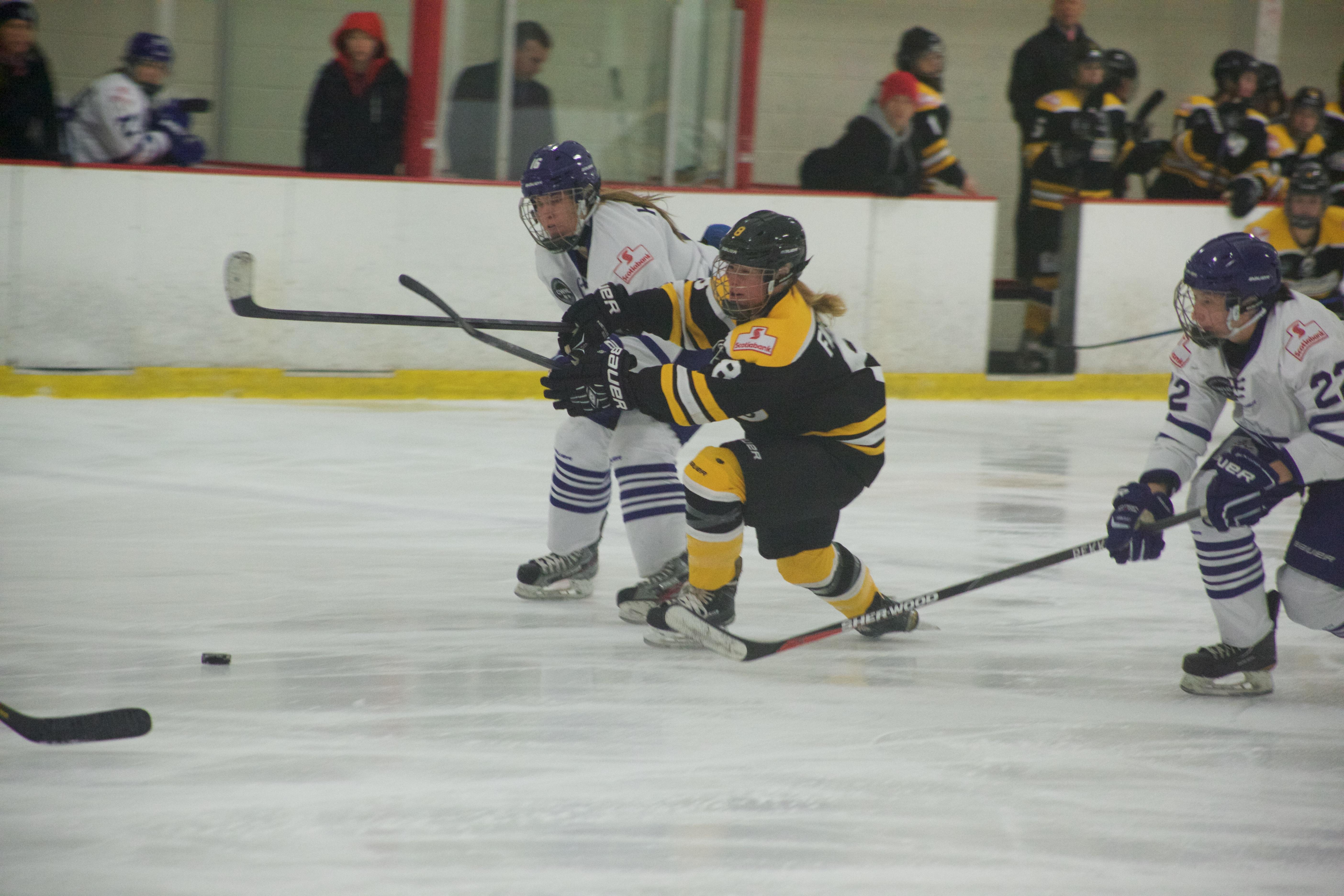 Boston Blades forward Rachel Farrel battles for the puck in Sunday's game.