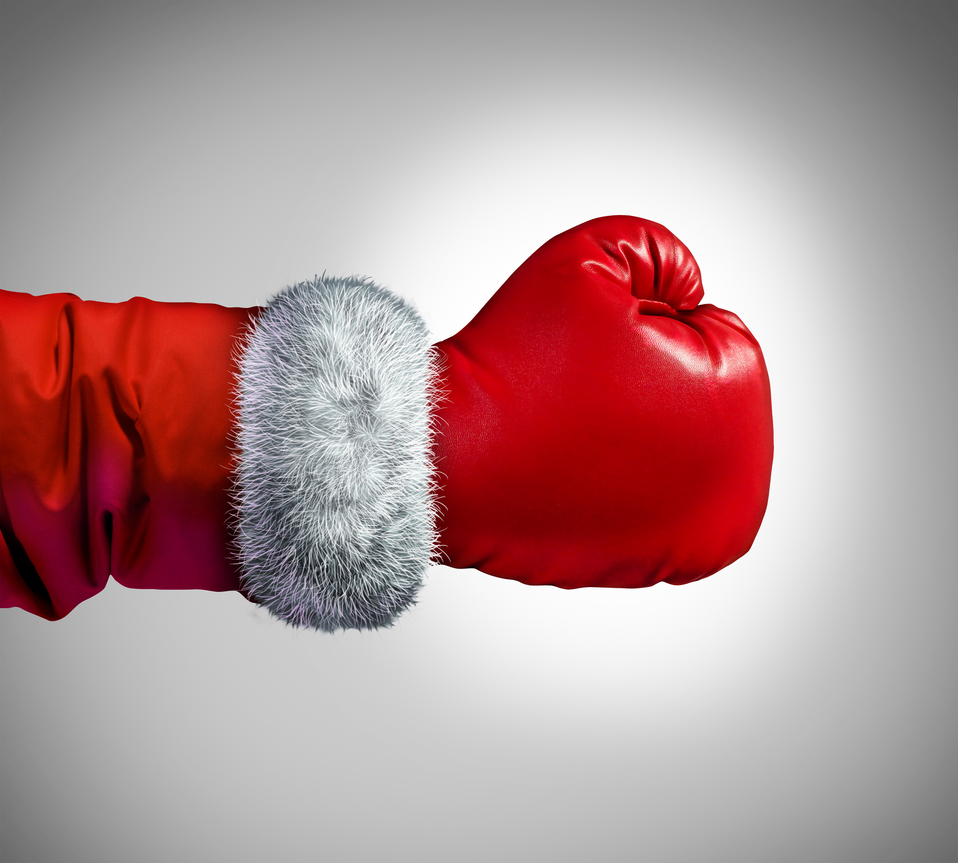 A boxing glove on the arm of someone wearing a Santa suit.