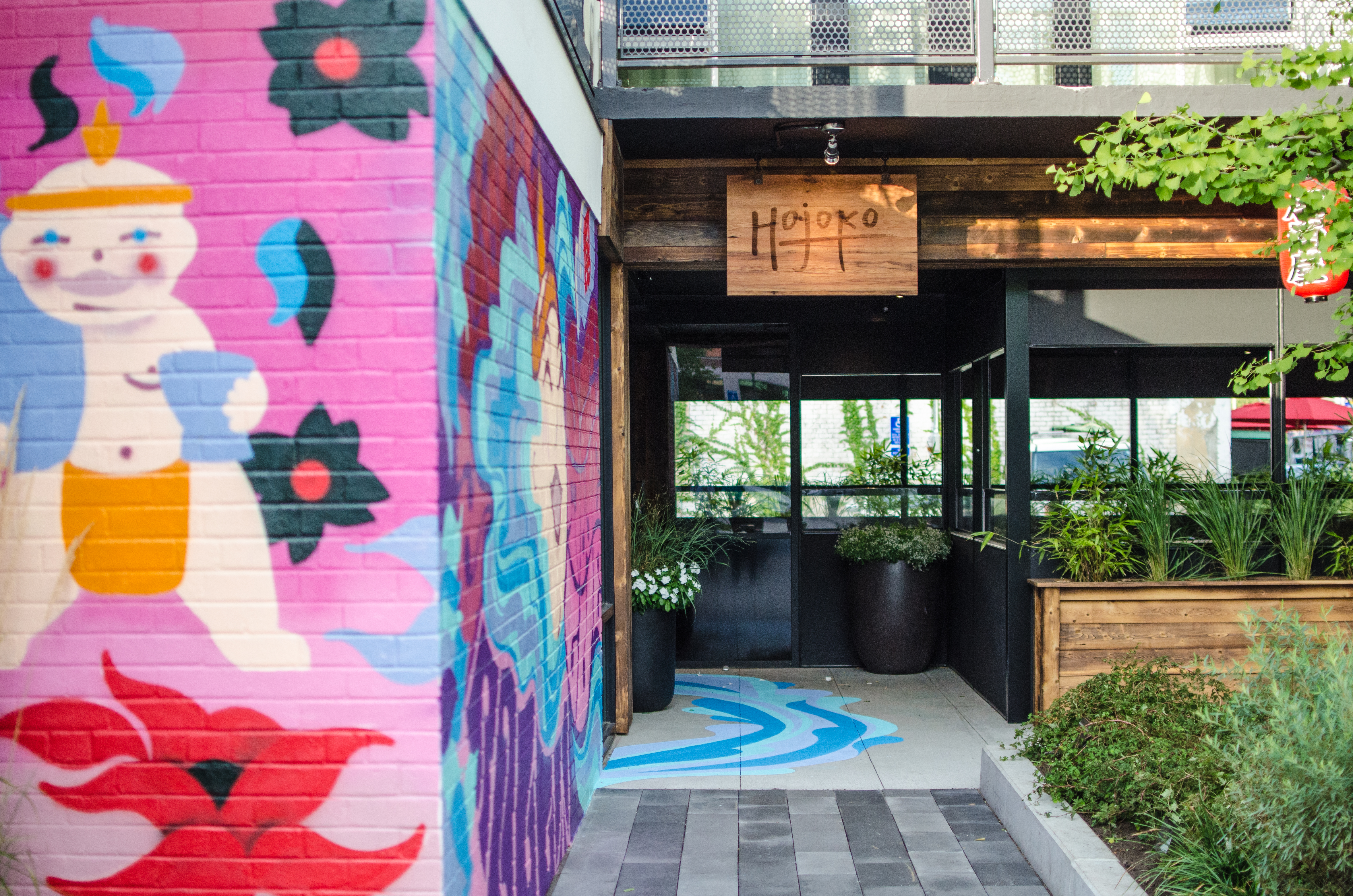 A colorful painted mural of a cartoonish sumo wrestler covers a brick wall leading towards the entrance of Hojoko in Boston's Fenway neighborhood