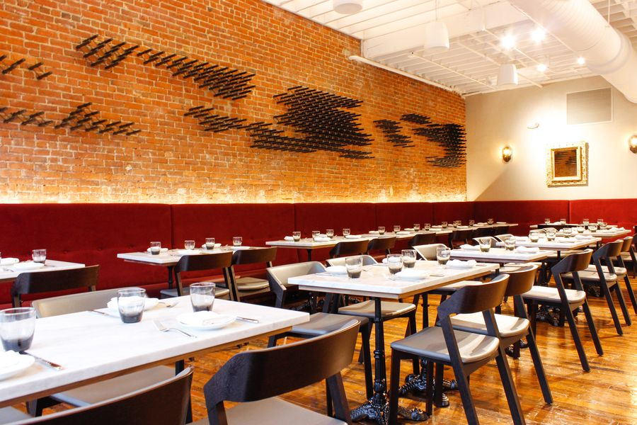 A sleek restaurant interior features a brick wall lined with wooden pegs for wine storage.