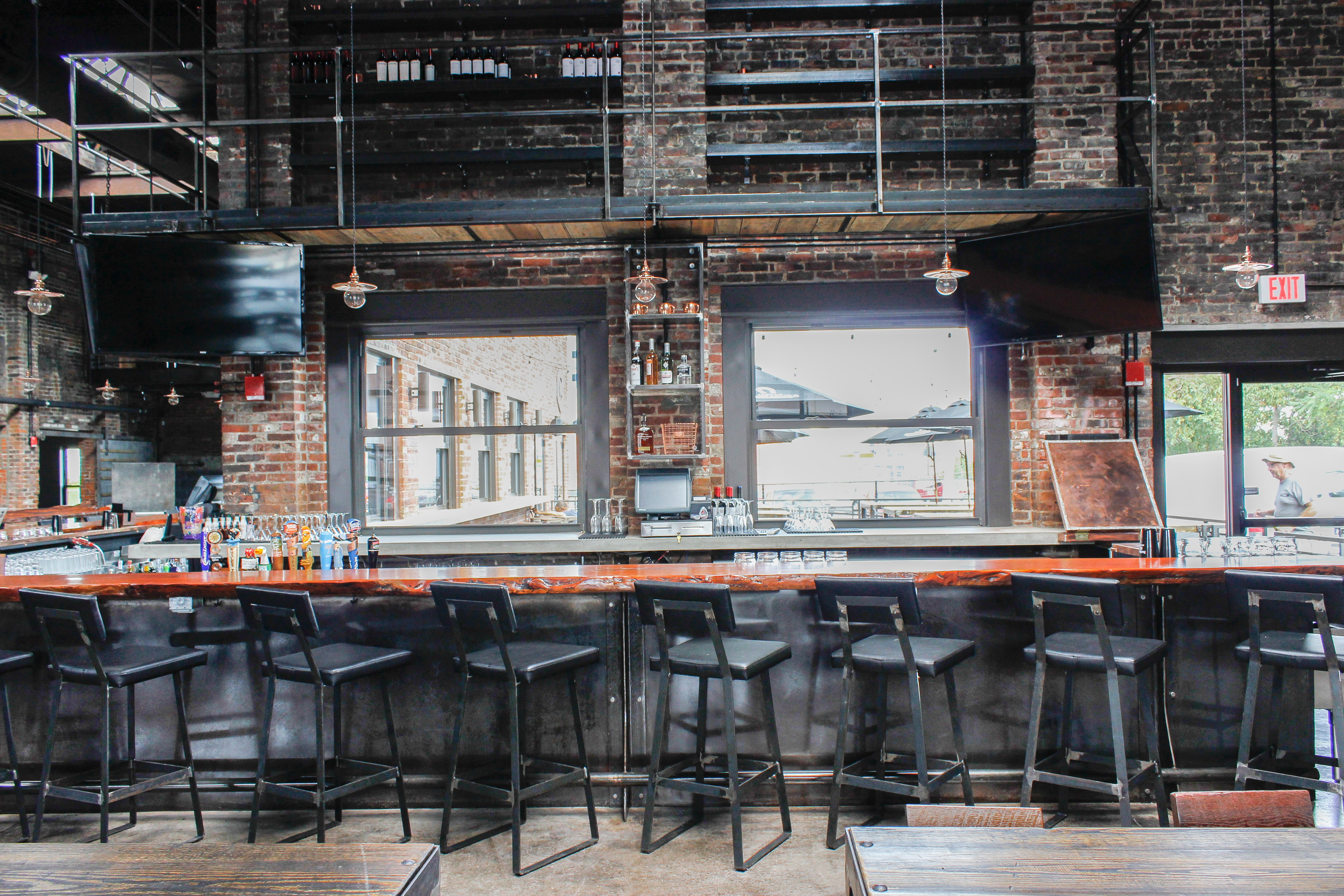 An industrial bar space, with wooden accents, lit by the sun shining through big windows on the back wall.