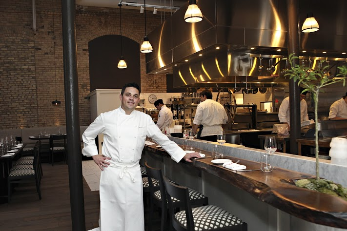 Gavin Kaysen leans on the bar seating in front of the open kitchen at Spoon and Stable