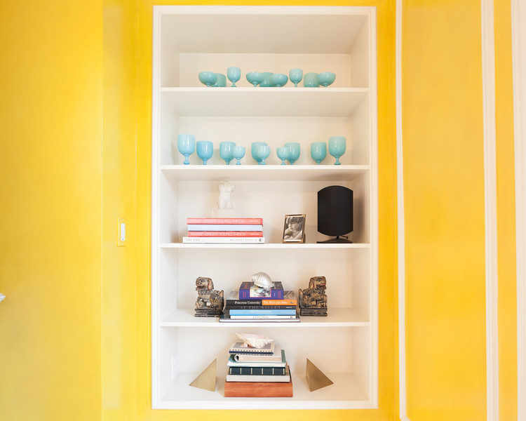 Shelves full of various objects and housewares. The walls on both sides of the shelves are bright yellow.