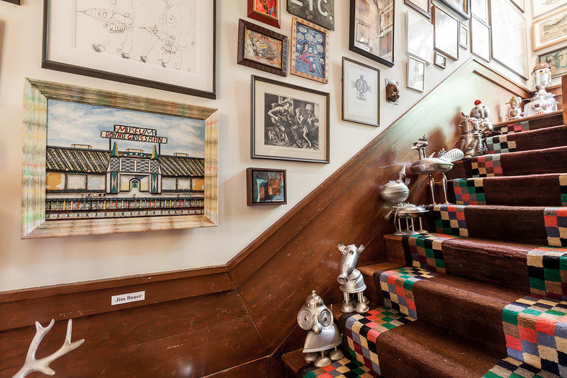 A staircase with various metal objects on each stair. The wall has multiple works of art hanging above the staircase.