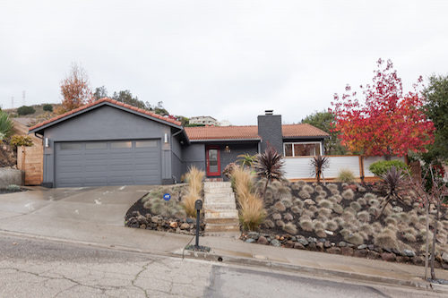 The exterior of a house in Oakland. The facade is grey and there is a red door. The roof is brown. There are trees and plants in front of the house.