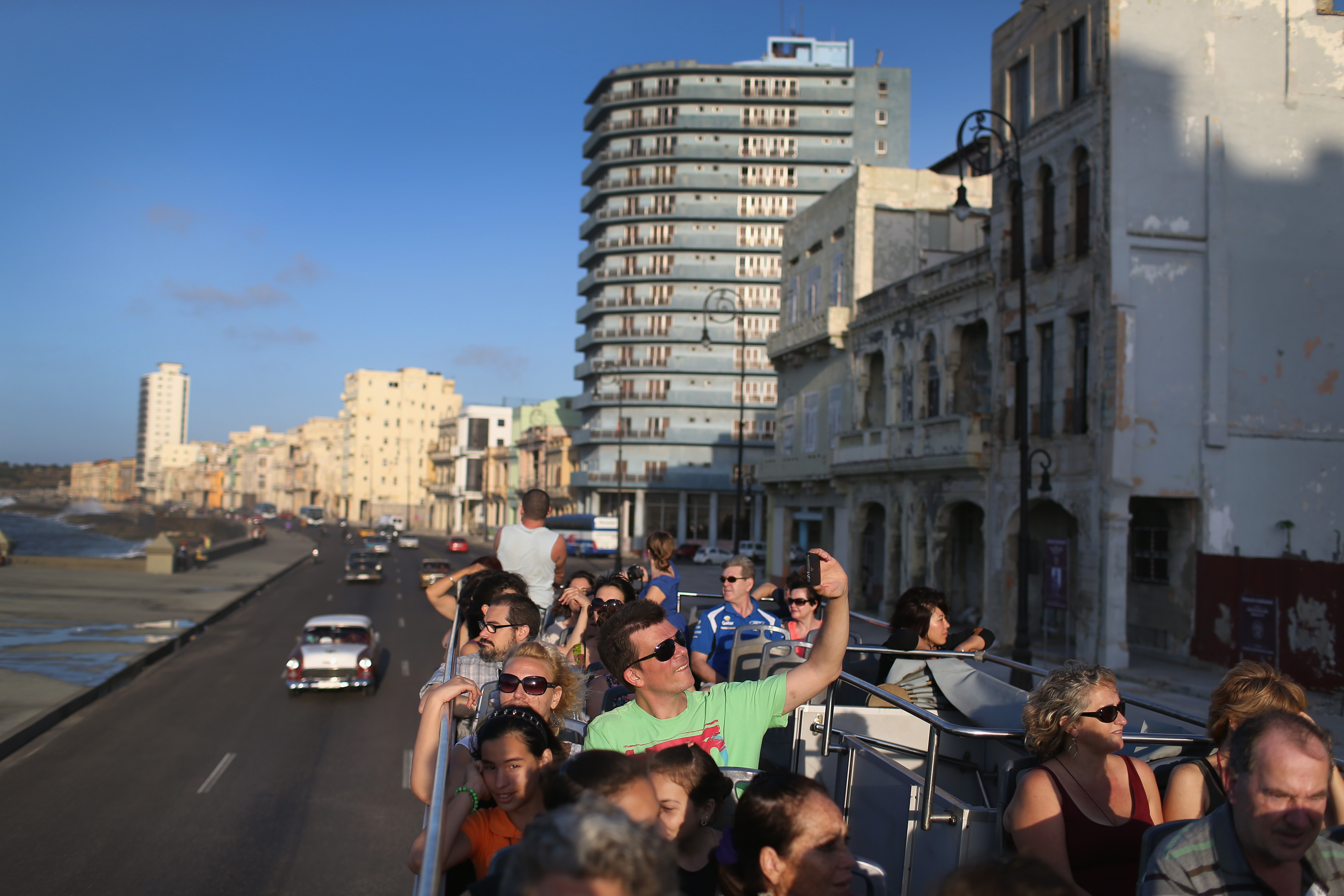 Tourists take in the sites from a double decker tour bus of Havana a day after the second round of diplomatic talks between the United States and Cuban officials took place in Washington, DC, on February 28, 2015.