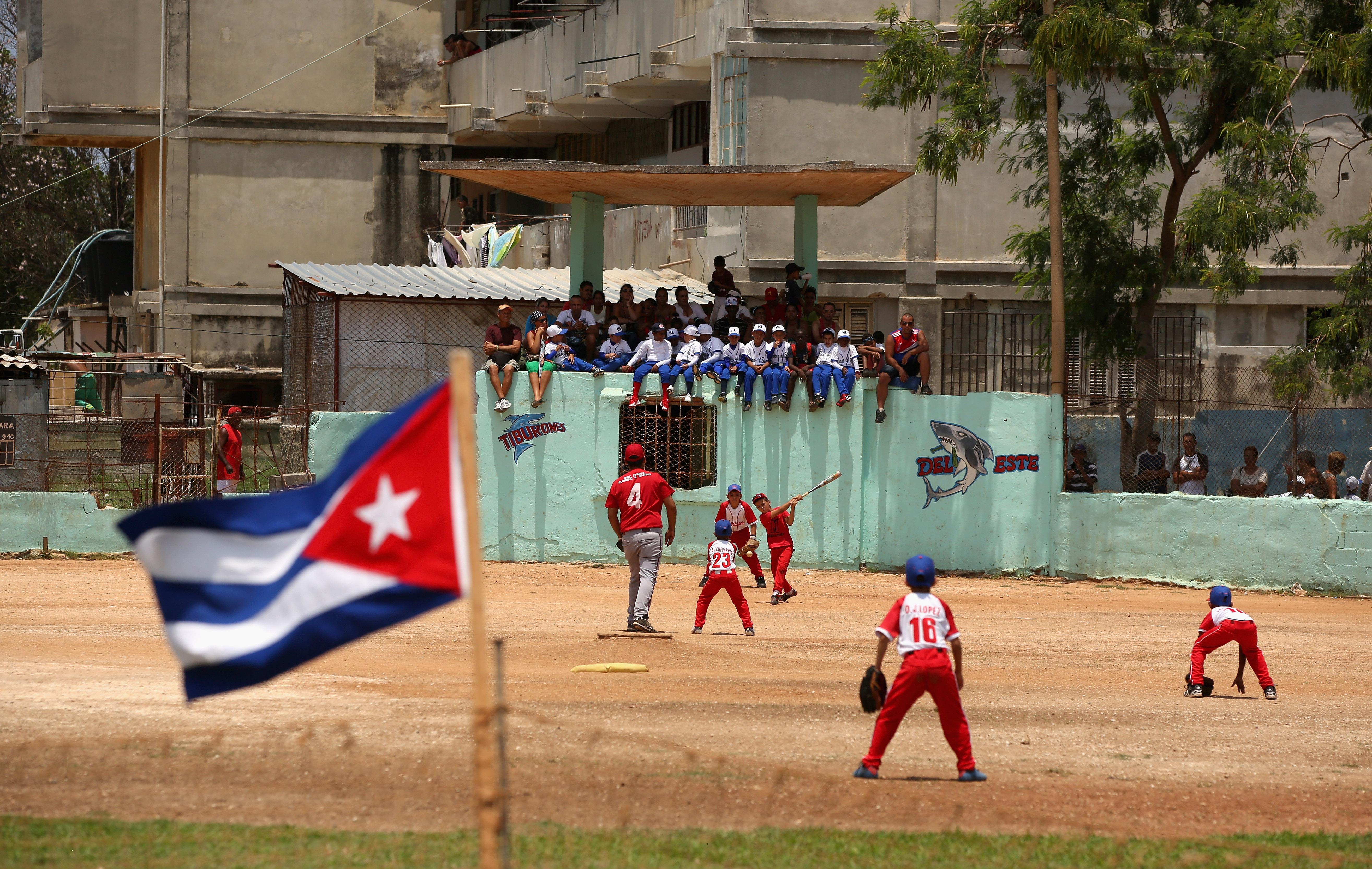 HAVANA, CUBA - MAY 09: The Cuban flag flies in the outfield as kids play baseball on May 09, 2015 in the Alamar subarb of Havana, Cuba.