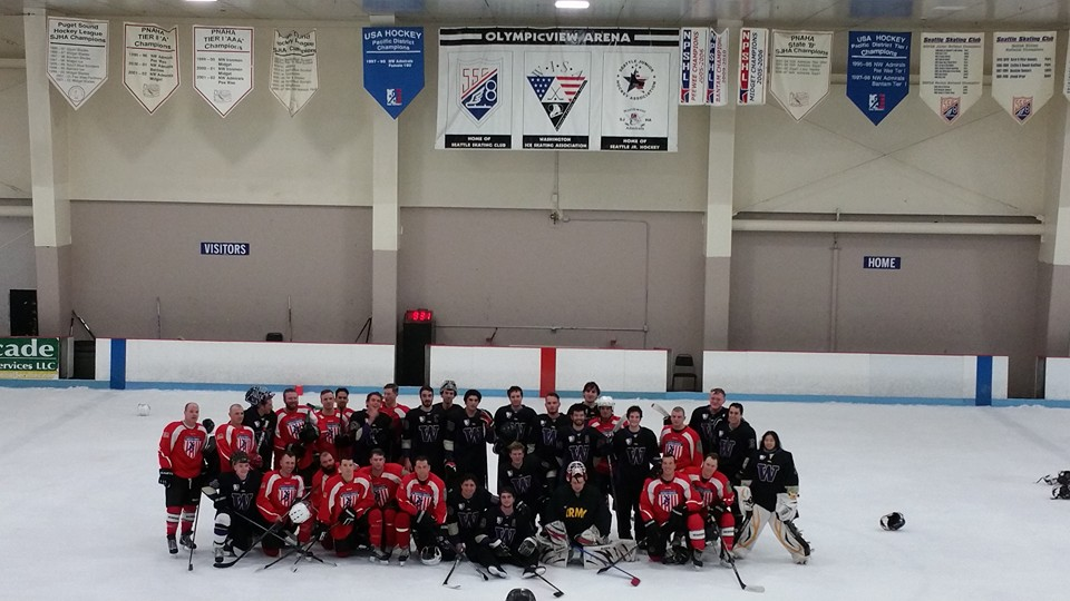 Washington Huskies players pose with the Hockey Saves, Inc. military/veterans team get together for a photo op immediately following an exhibition game at Olympicview Arena on Saturday night.