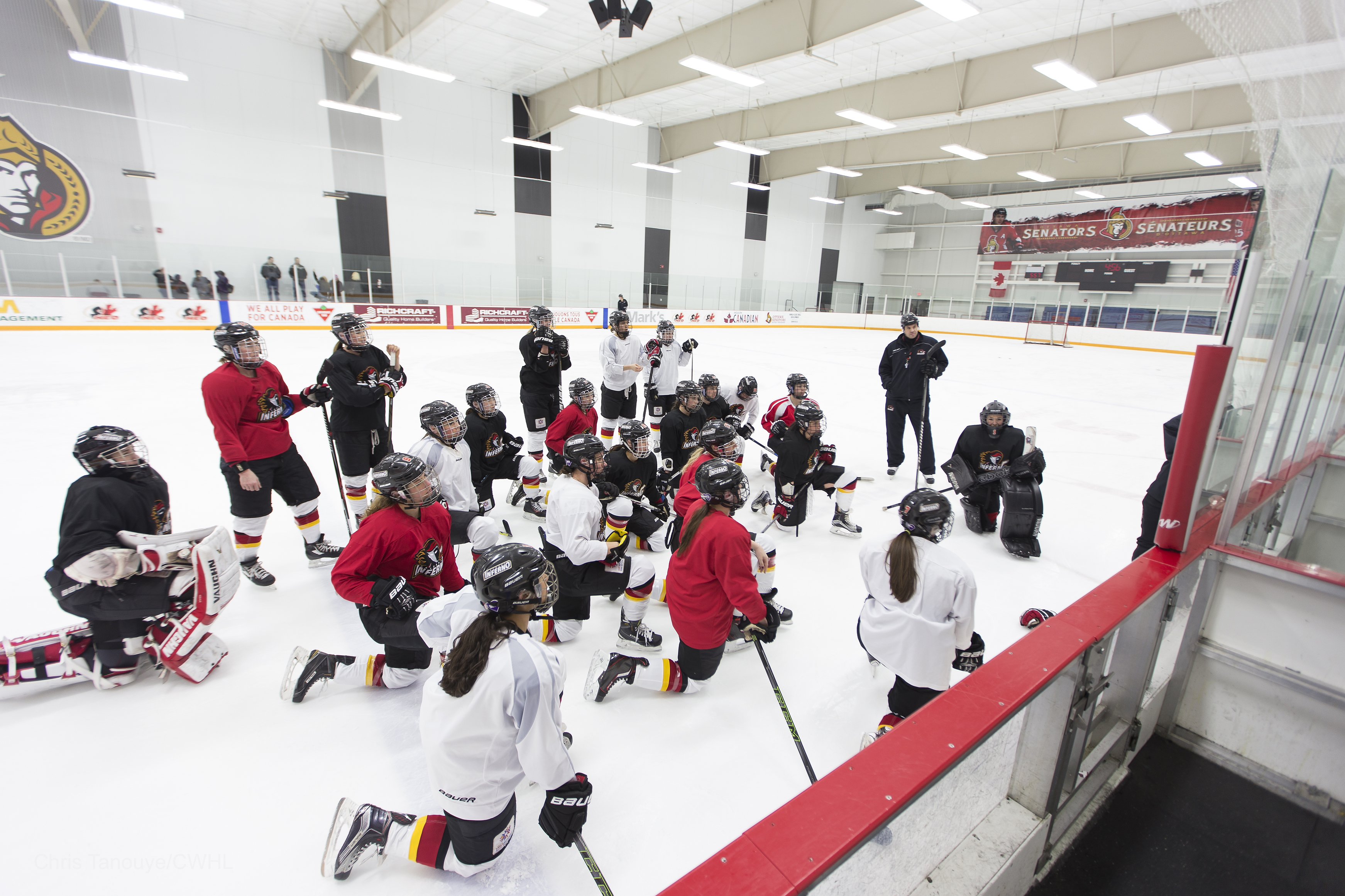 The Calgary Inferno look on as head coach Scott Reid outlines a drill for the final practice before the Clarkson Cup Final in Ottawa Sunday.