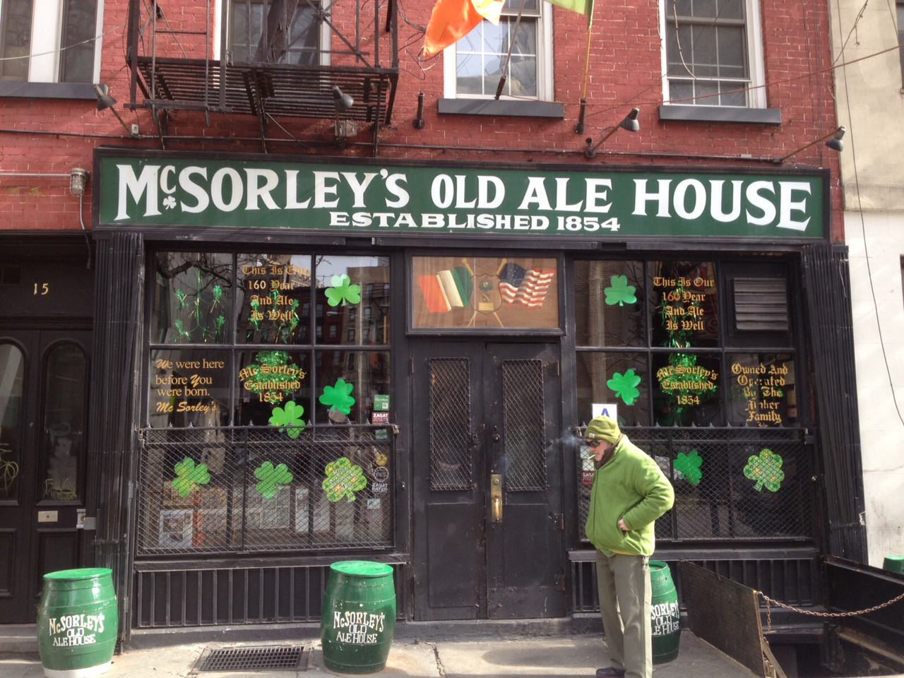 """A man dressed in green walks in front of a restaurant decorated for Saint Patrick's Day, with a sign that reads """"McSorley's Old Ale House"""""""