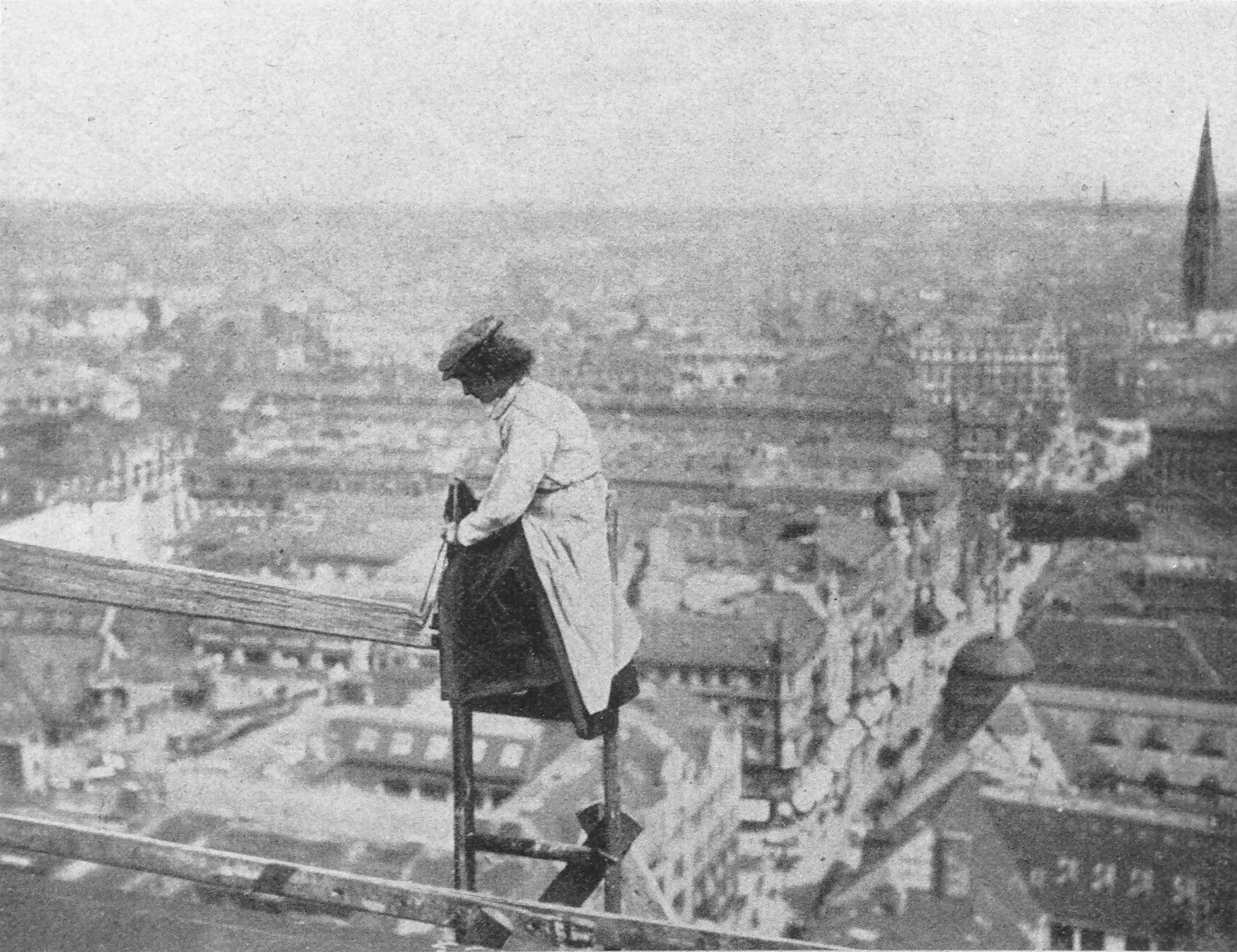 Recalling Fay Kellogg in New York City, a female builder in Berlin shows off her daring to the press. She is pictured making repairs to the roof of Berlin's City Hall in 1910