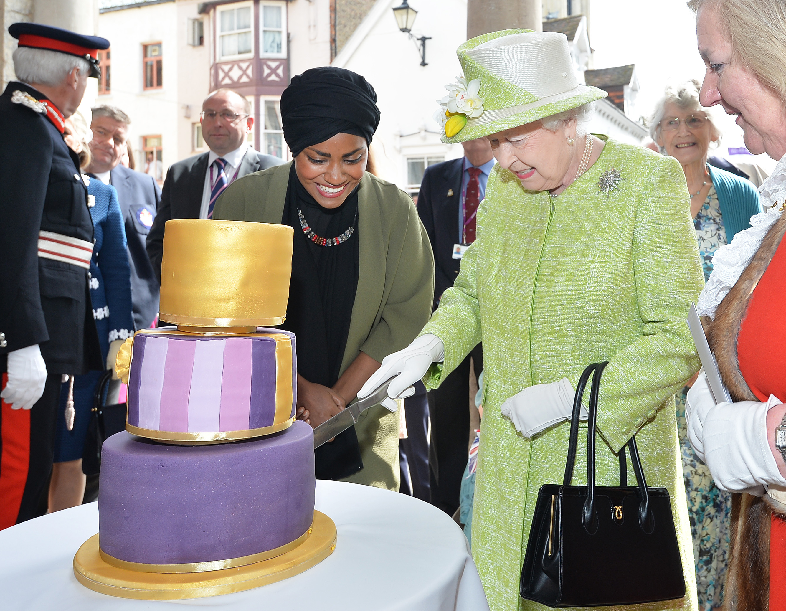 Someone, please help the Queen out. Cutting through fondant isn't easy.