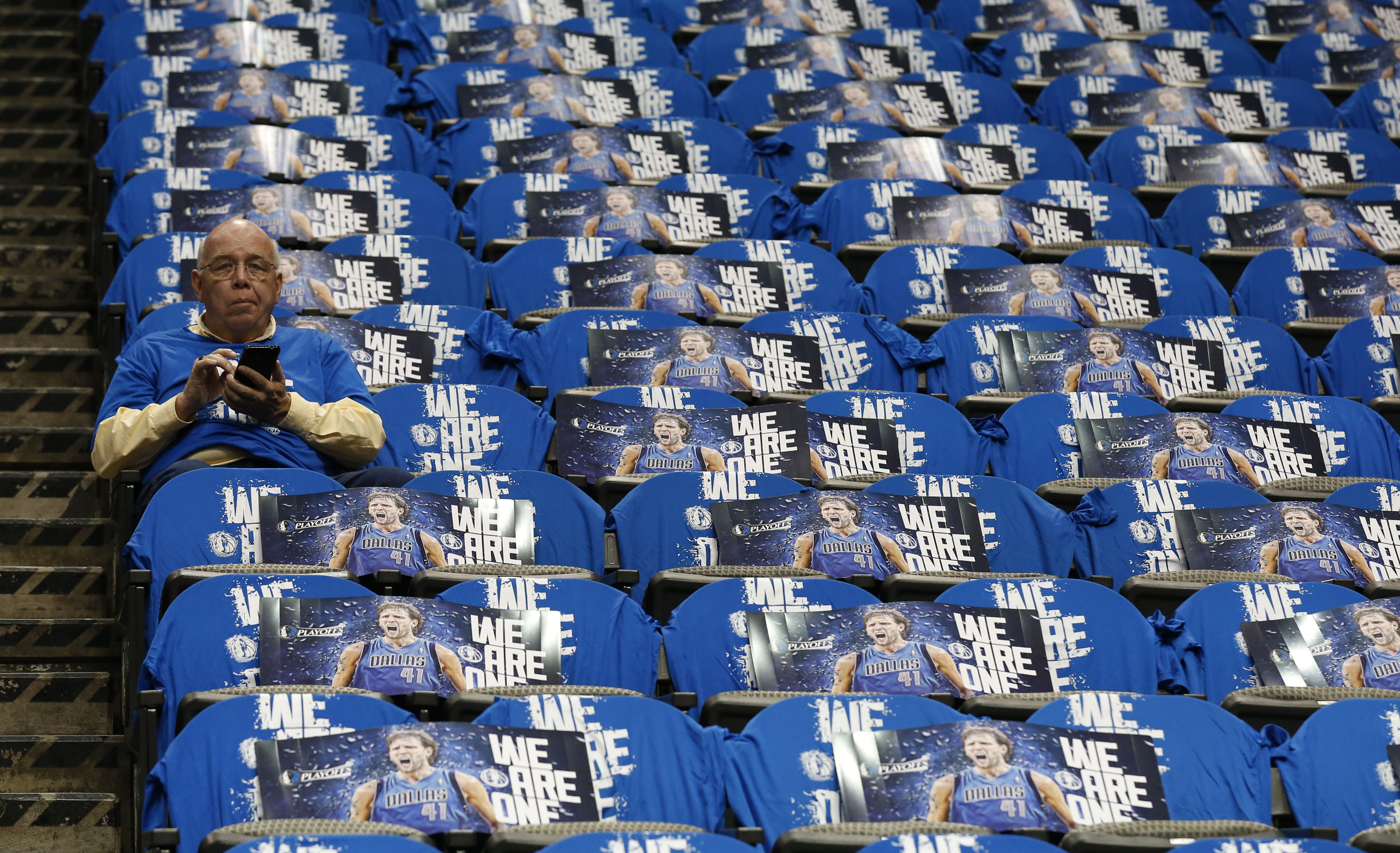 A loyal Mavs Moneyball reader catches up on the latest news on his phone before a Mavericks game.